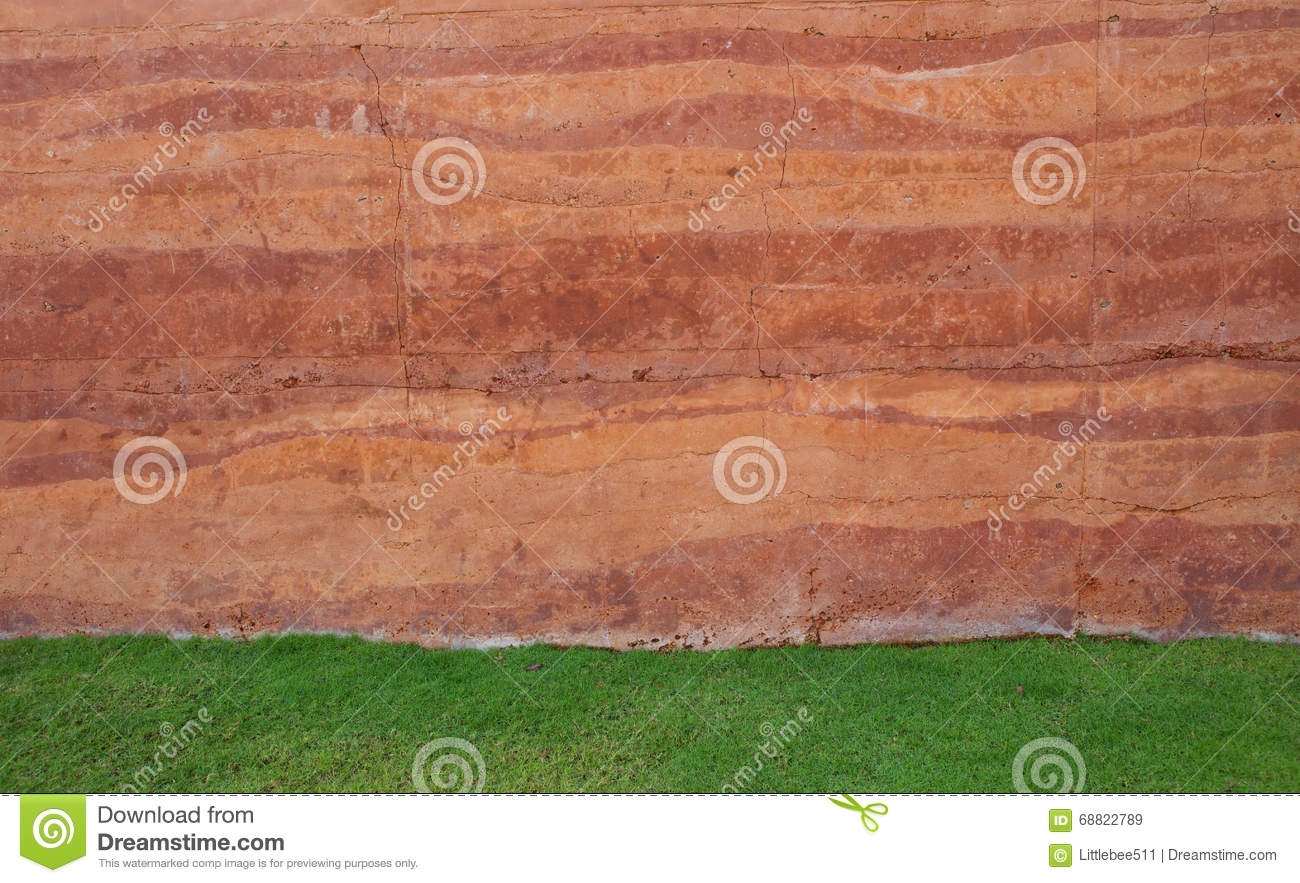 Red soil wall background and green grass field stock image for Soil and green