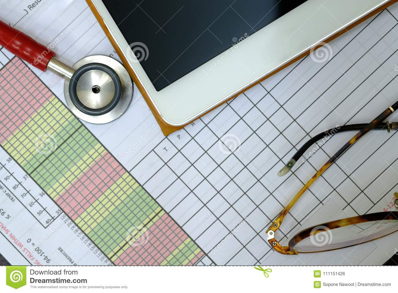a red stethoscope a patient vital sign sheet and a tablet stock