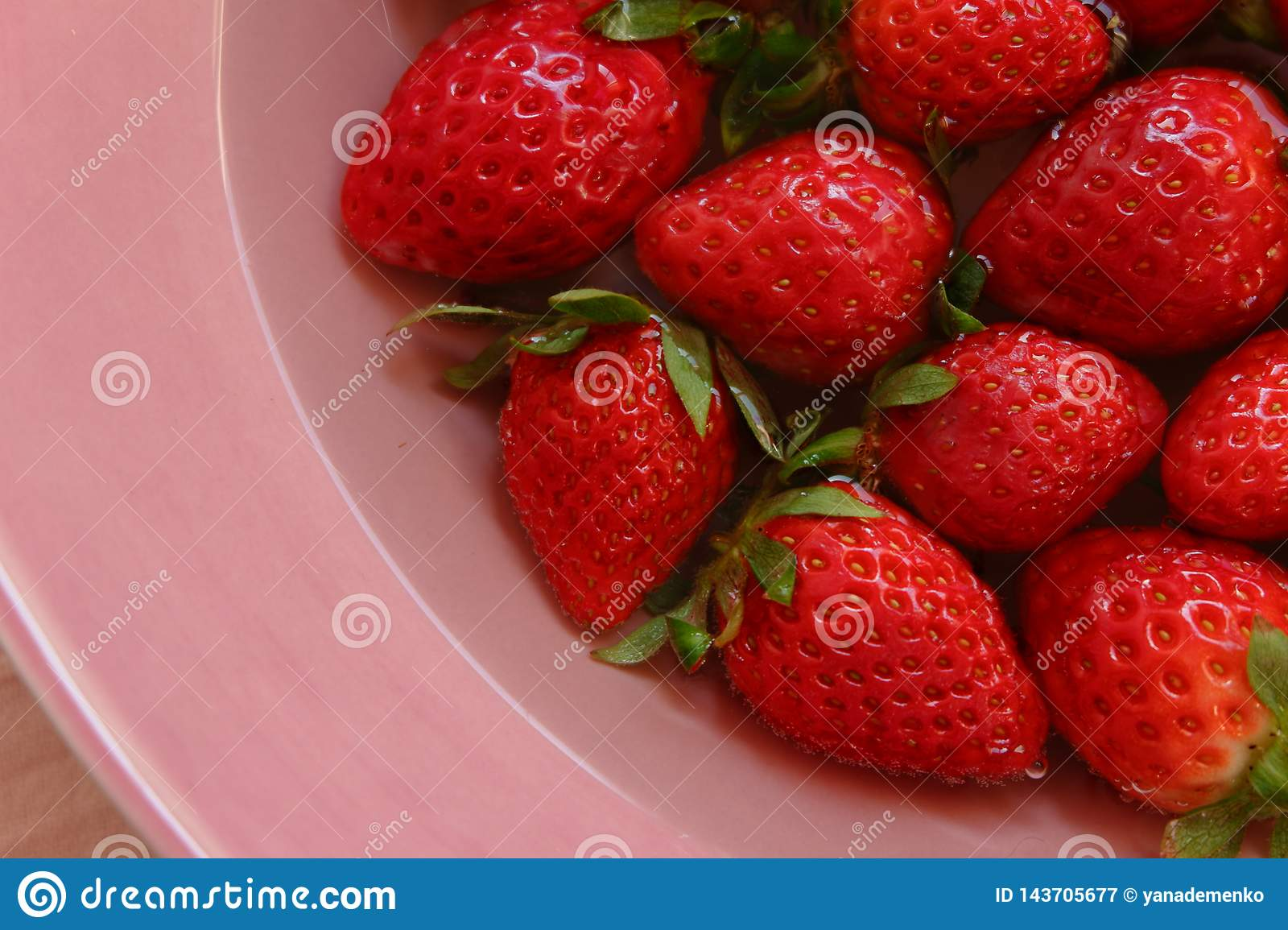 Red strawberies of the different size on the plate