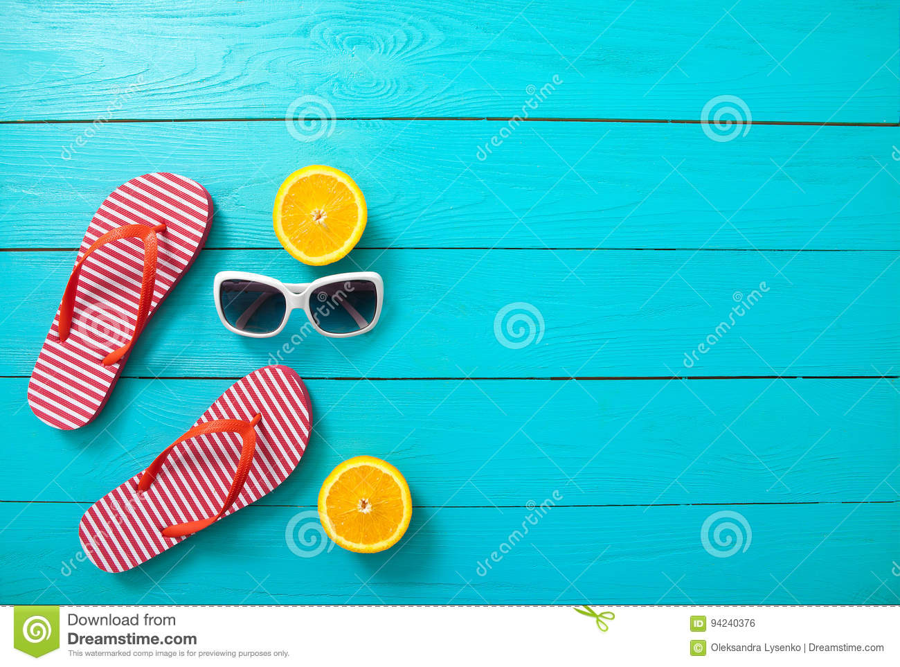 Red striped flip flops, red sunglasses and orange fruit on blue wooden background. Top view and summer time.