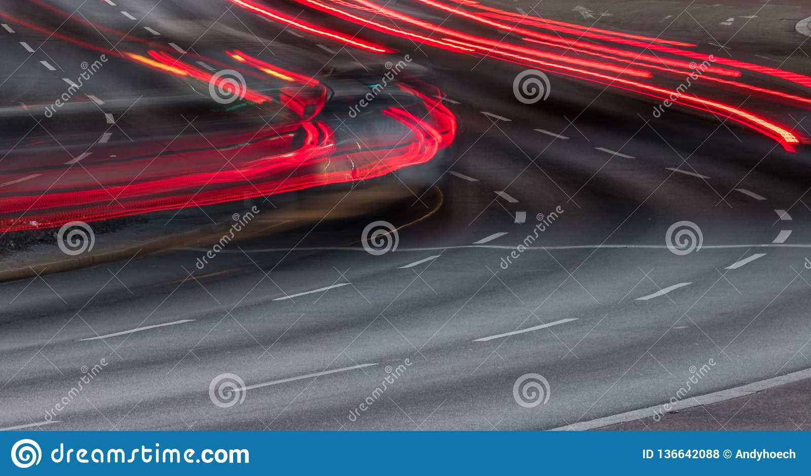 The red taillights on the three lane road