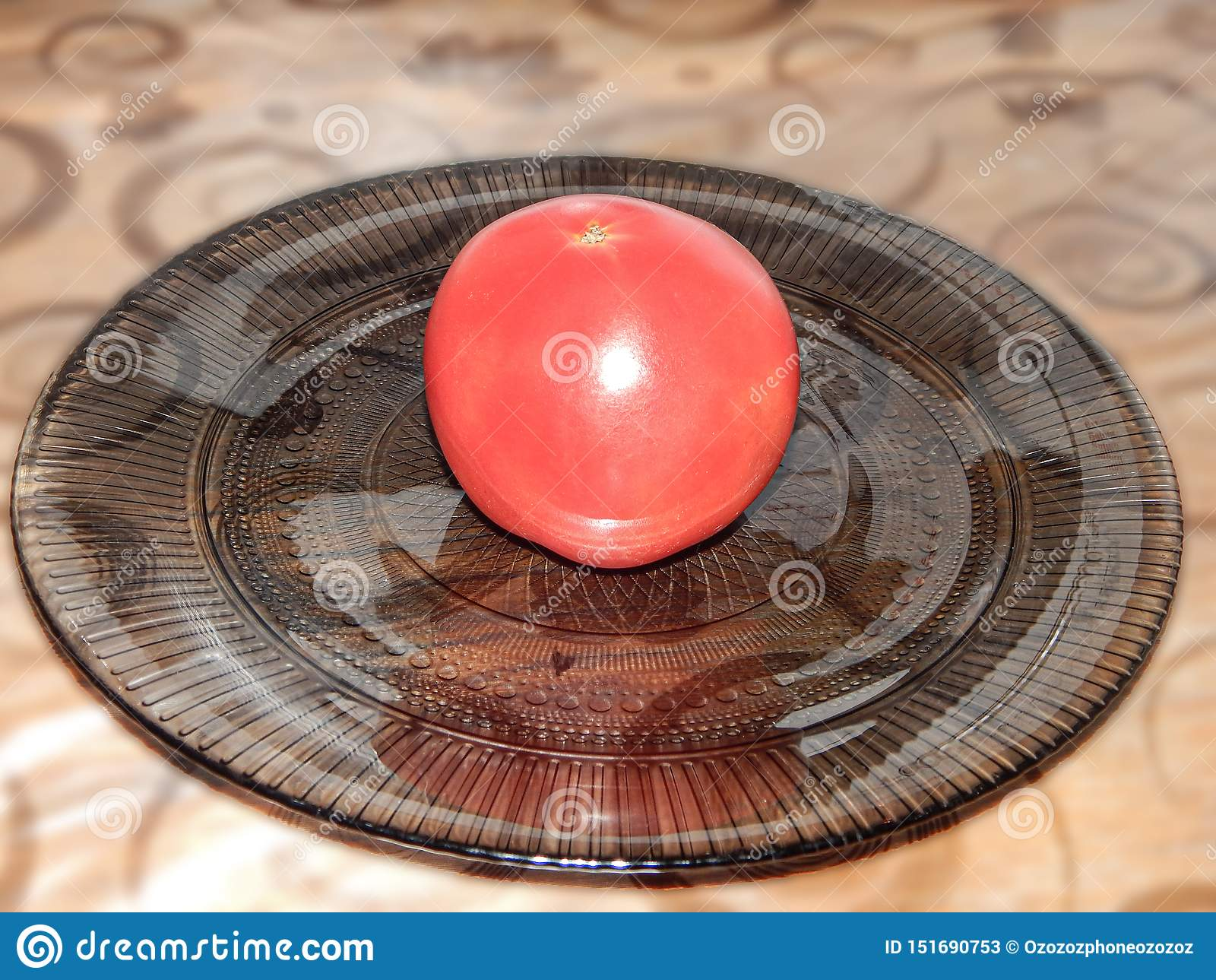 Red tomato on a plate on the table