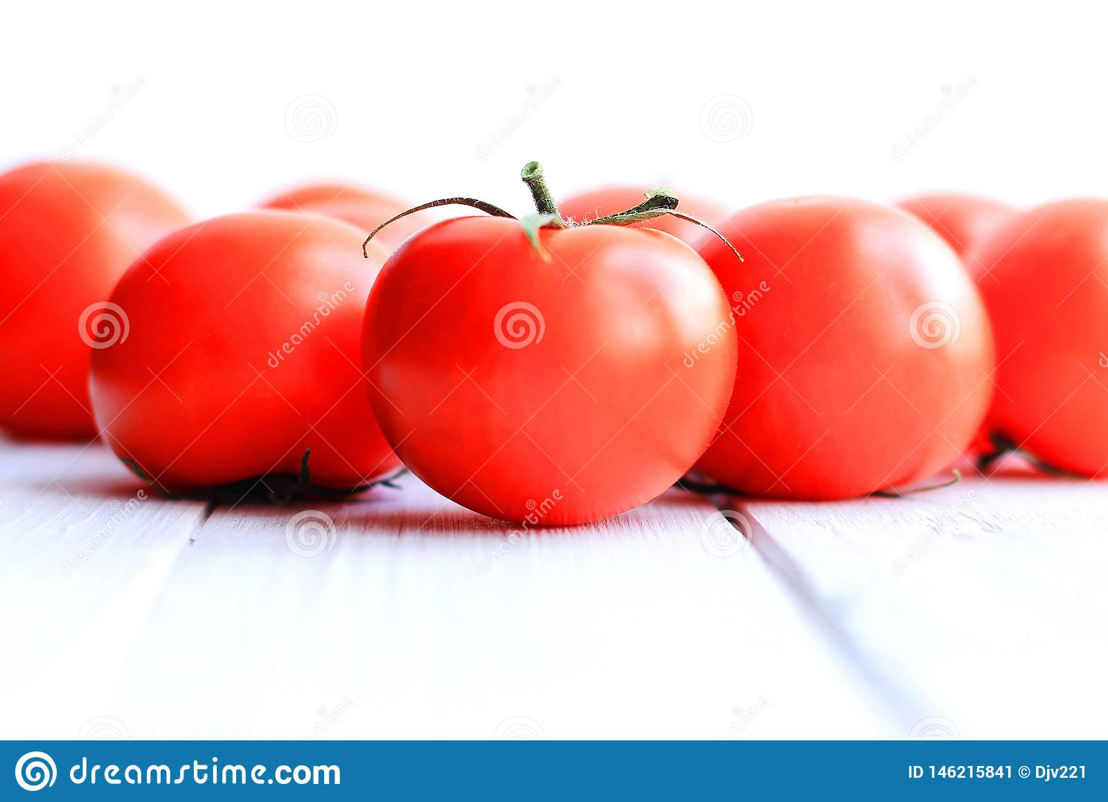 Red tomatoes on a light wooden background