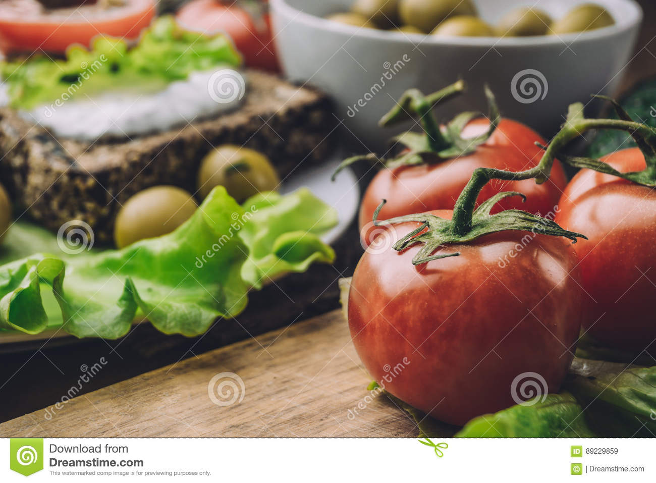 Red tomatoes on wooden board and bread with sauce, olives in bowl on kitchen