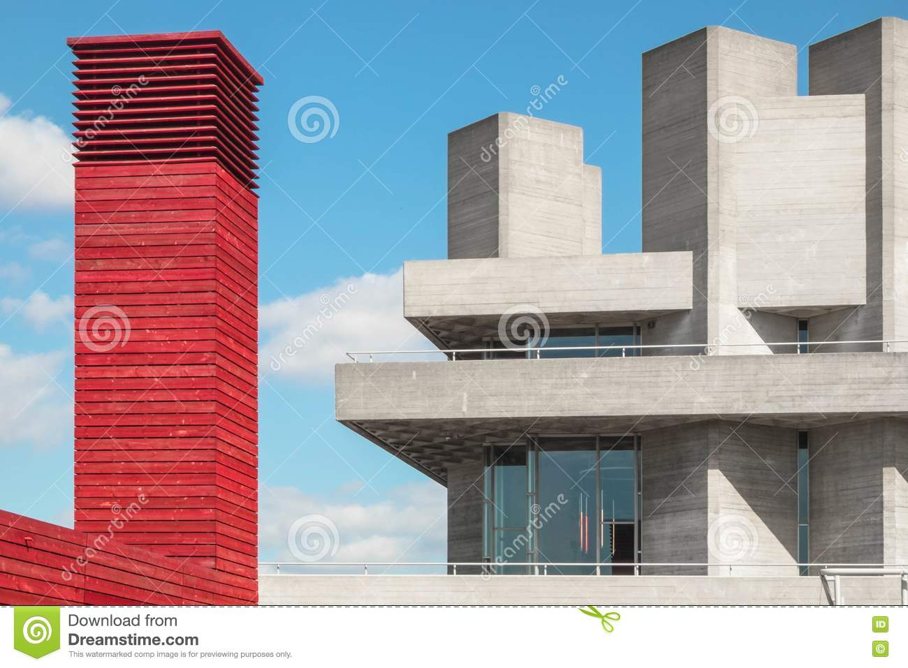 Red tower made of wood beside a concrete building with concrete towers and blue sky with white clouds