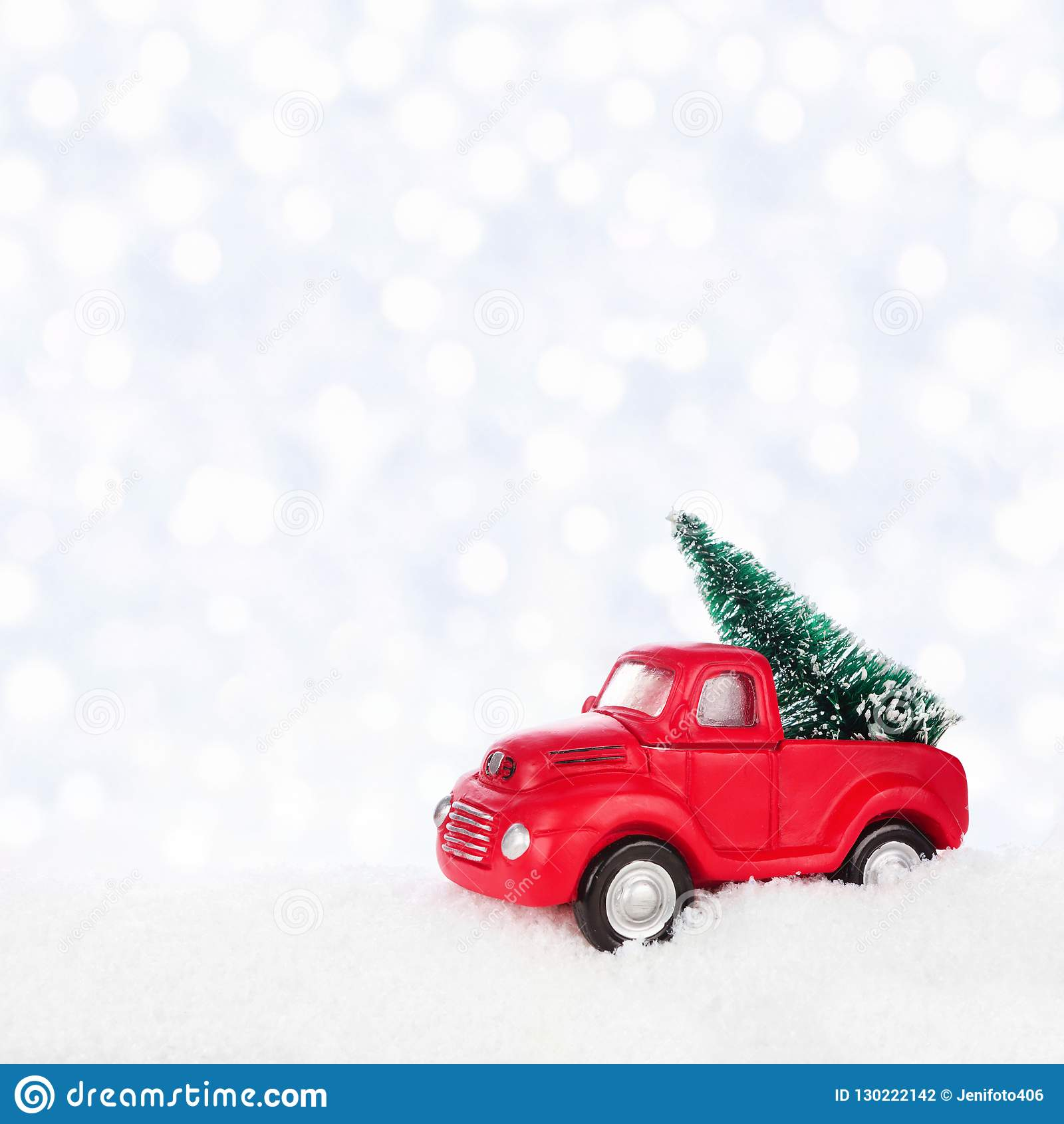 red toy truck christmas tree snow against silver twinkling light background 130222142