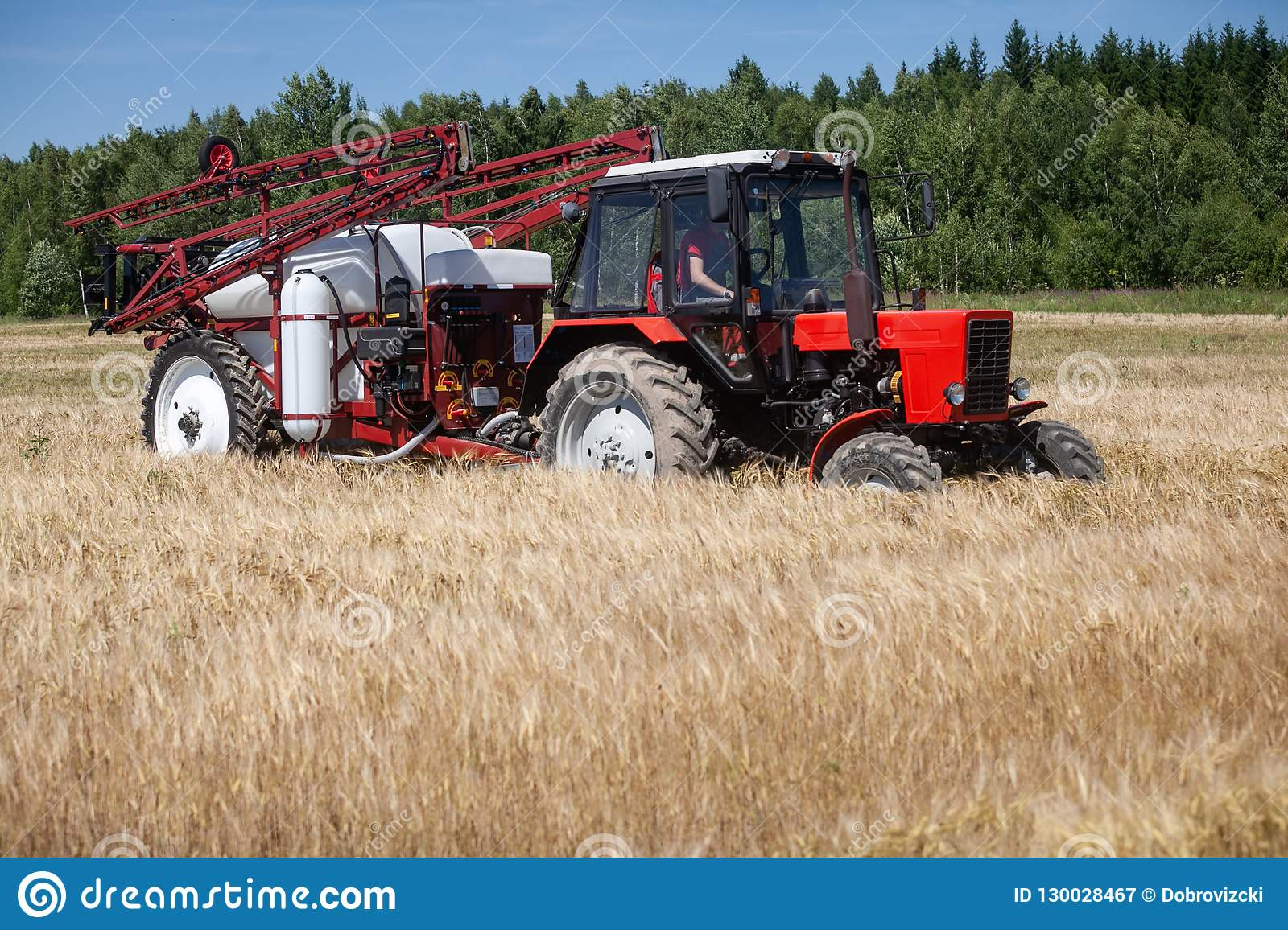Red tracktor sprayer in the field