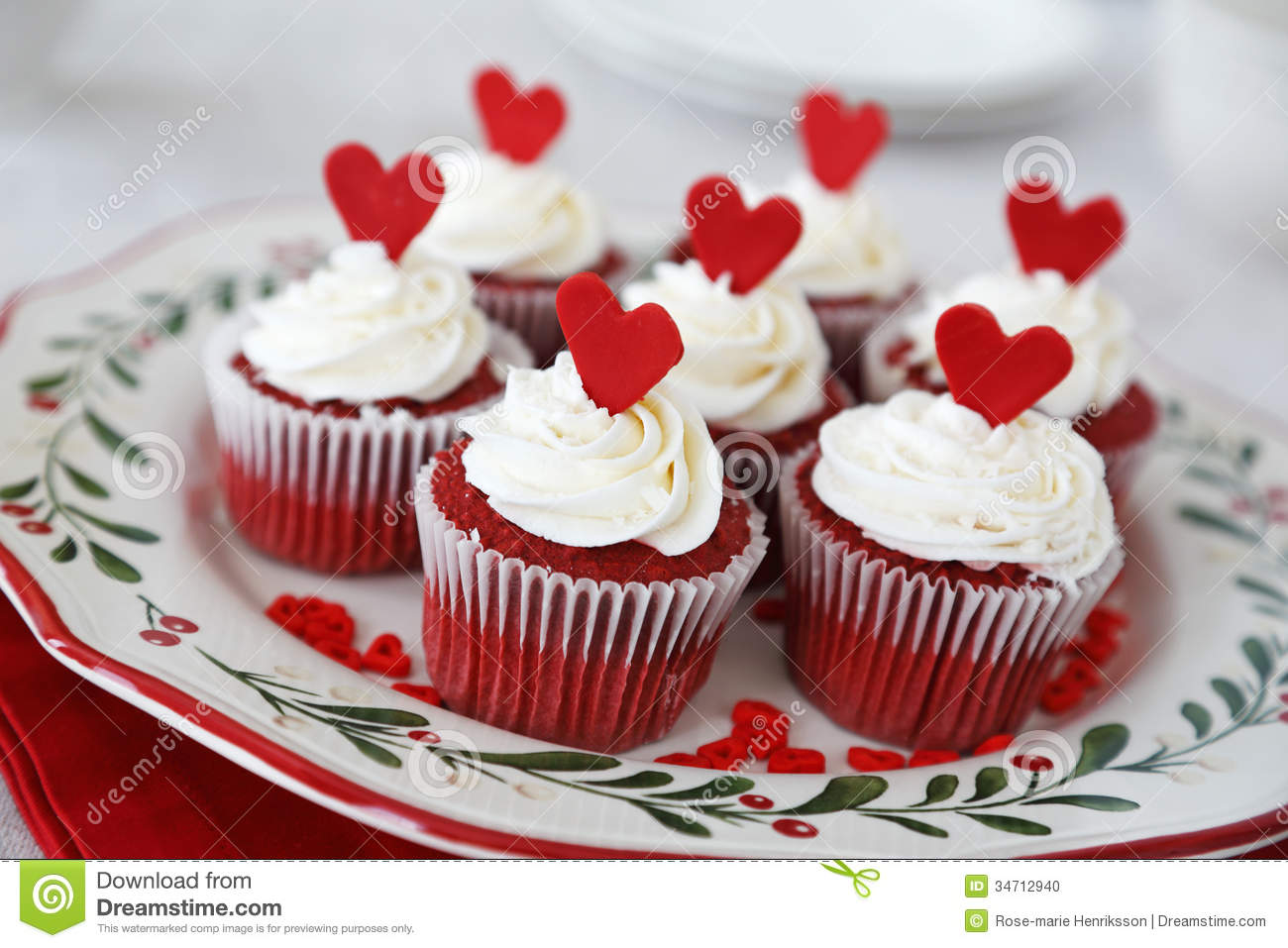 Red velvet cupcakes decorated for Christmas with red hearts.