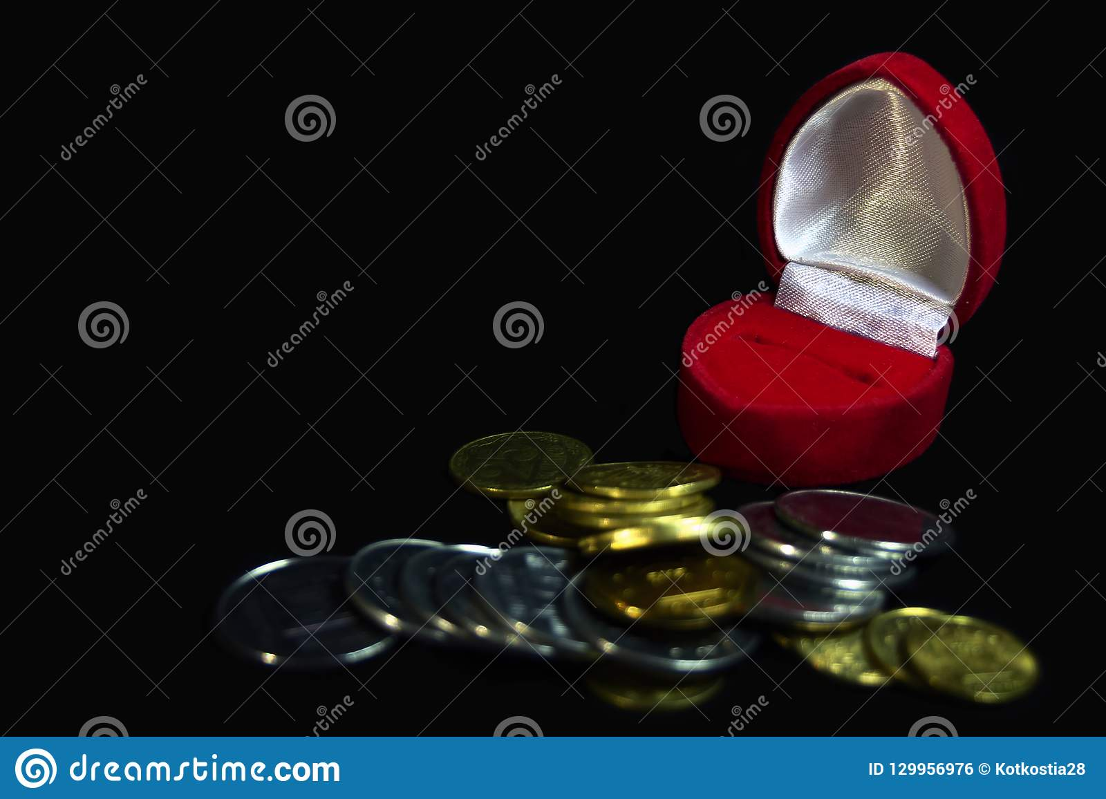 Red velvet gift box for a ring on a black background with coins of different denominations symbolizing a marriage of convenience,