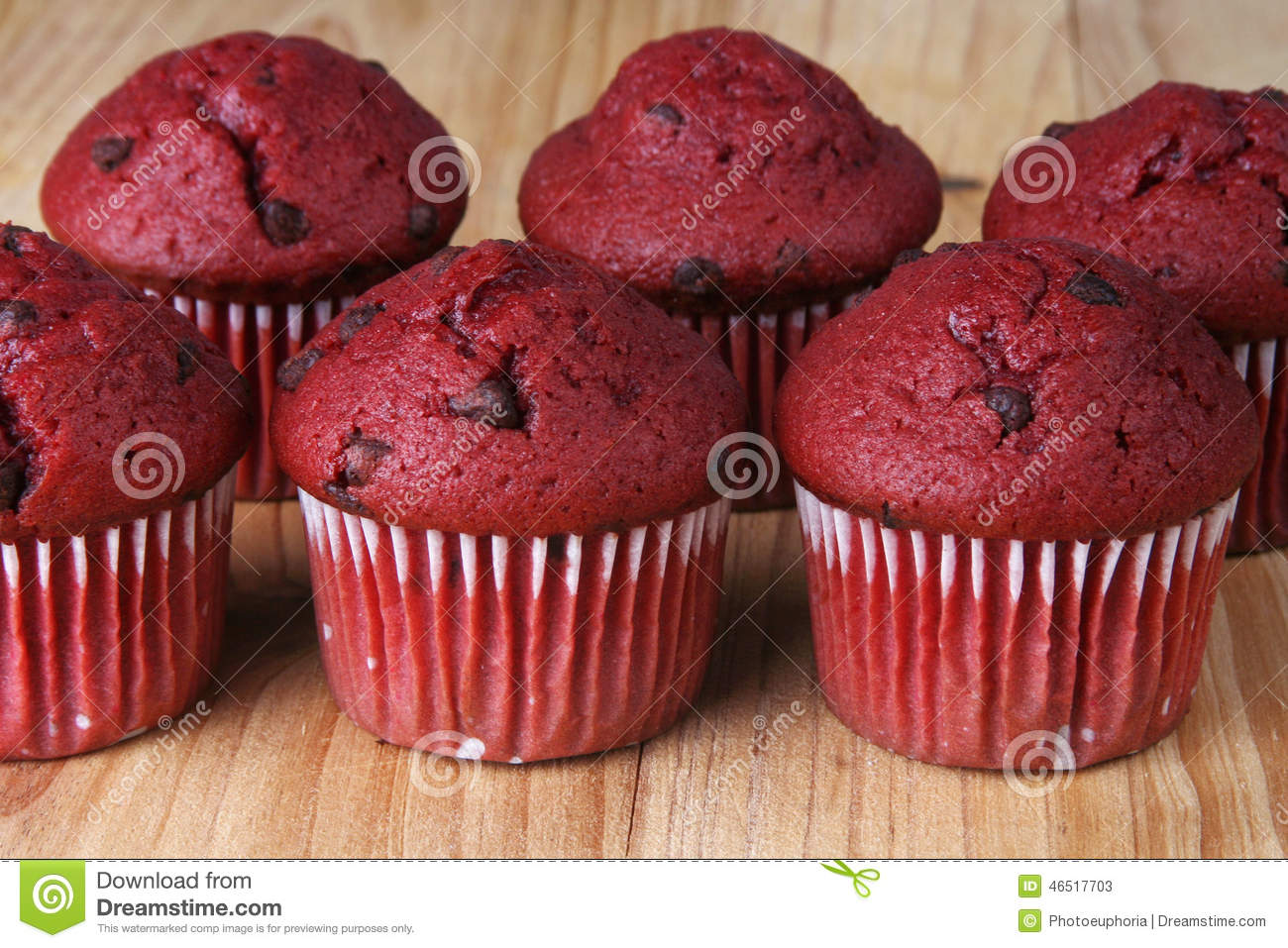 Shot of several red velvet muffins on a wooden board.