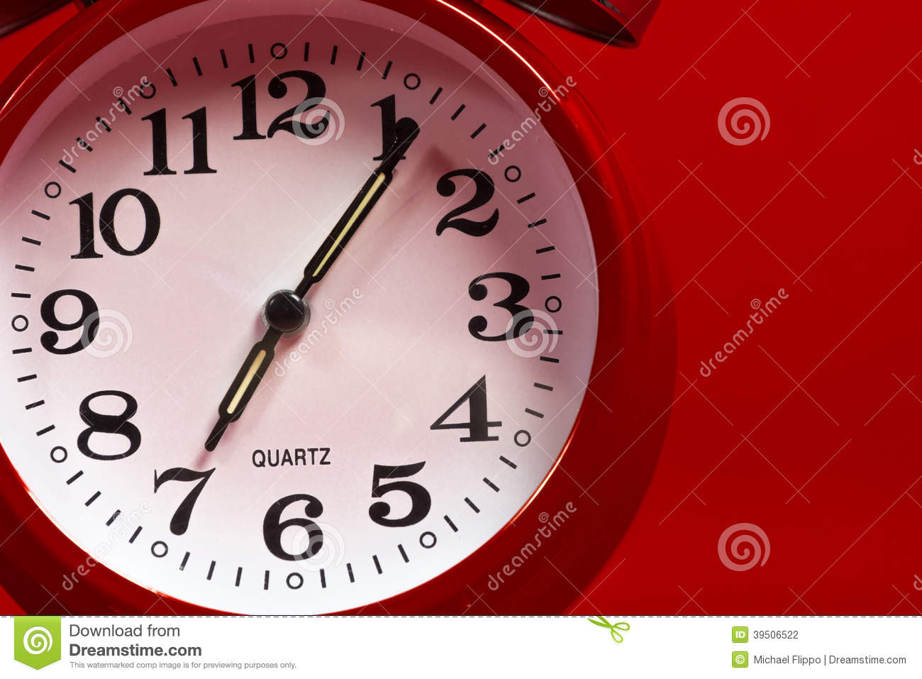 A red vintage alarm clock on a red background