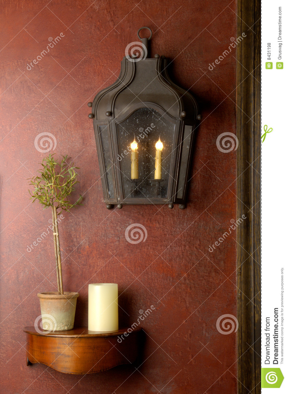 Red wall with lantern and small wooden shelf.