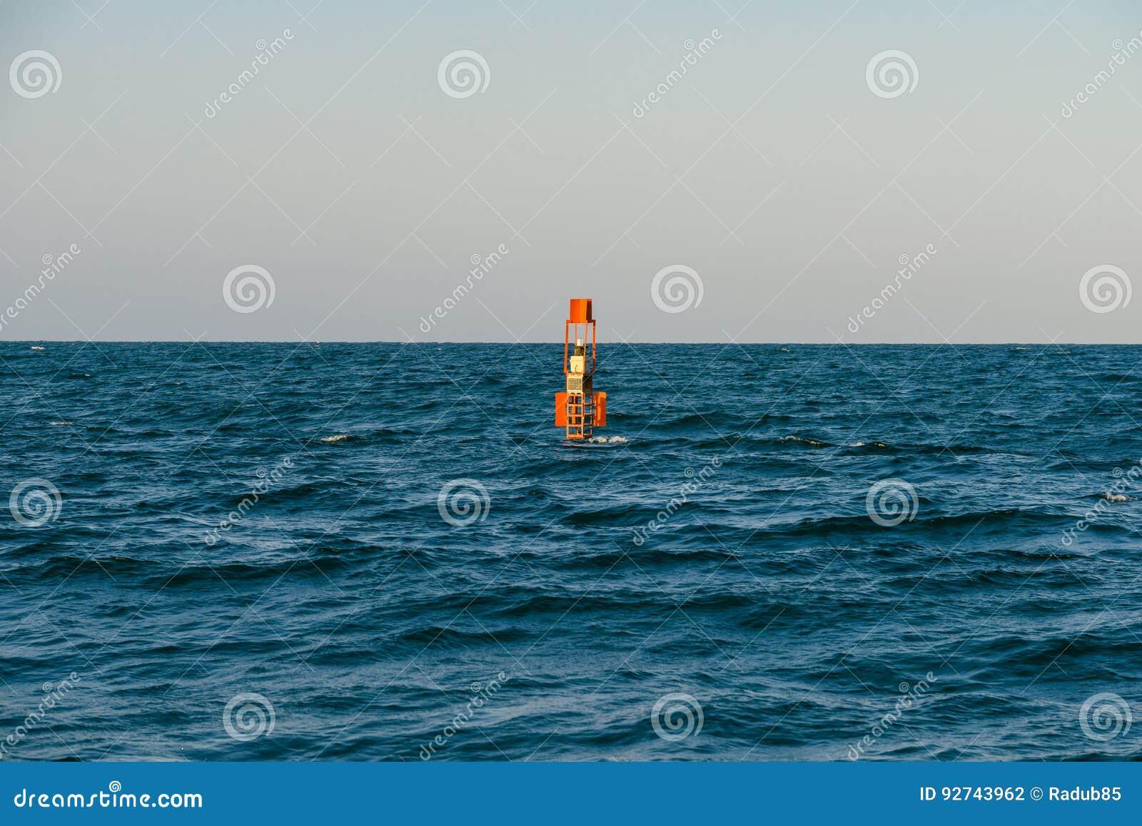 Red Warning Light Floating In Ocean Stock Photo
