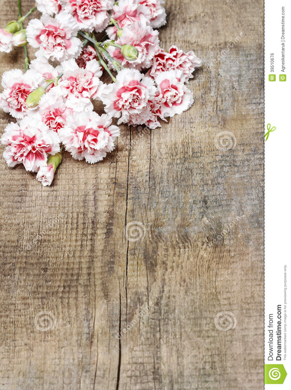 Red and white carnations on wooden table