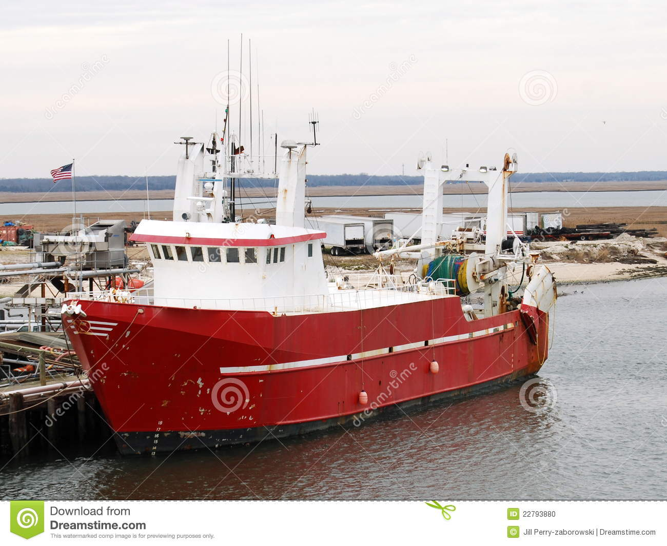 red & white commercial fishing, scallop, boat docked on the water.