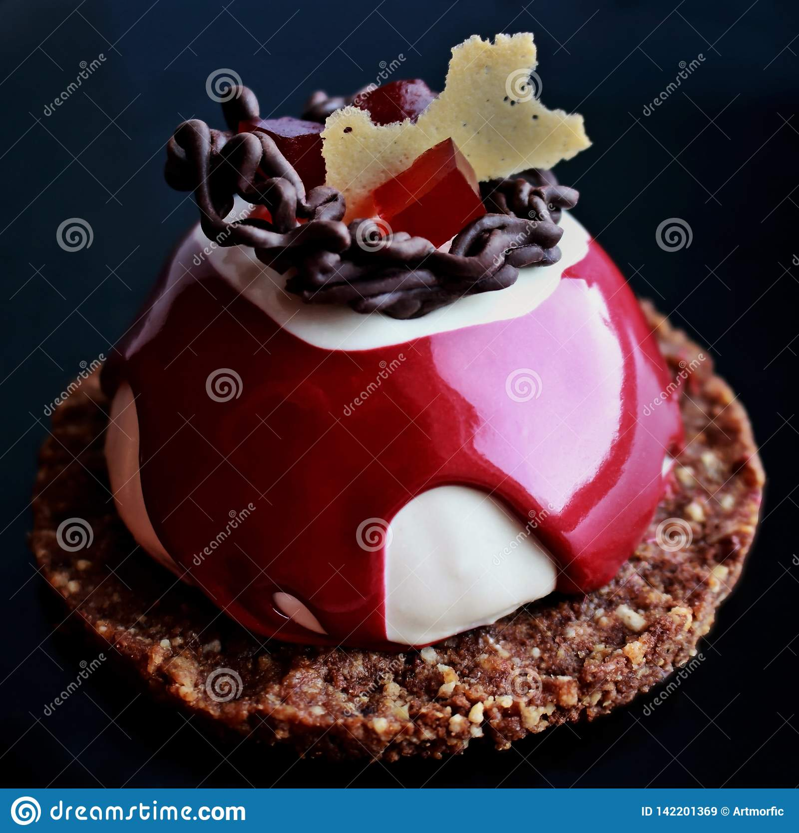 Red and white dessert with chocolate decoration, red jelly and cookie base