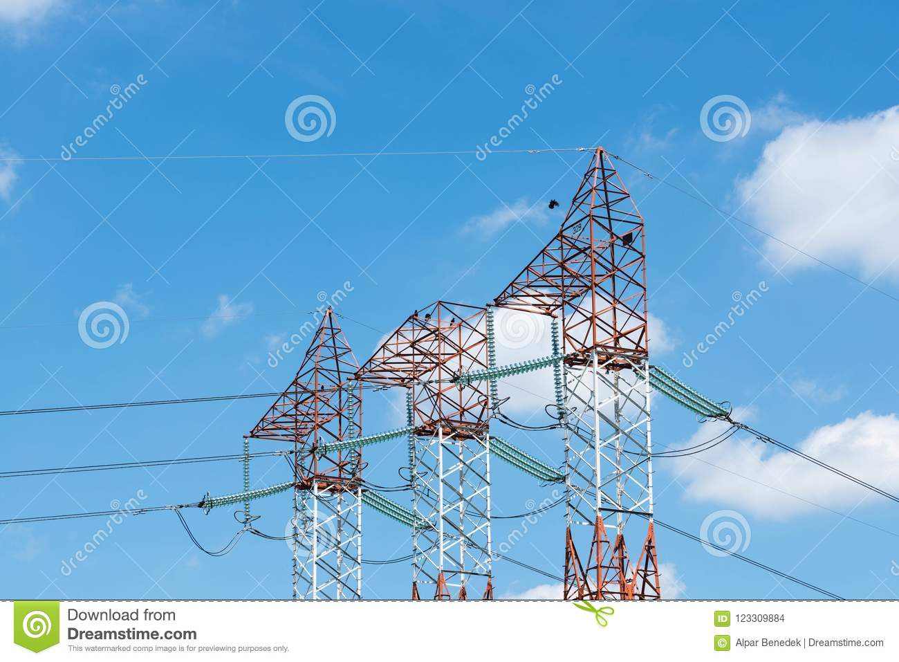 Red white electricity pylons, blue sky with white clouds