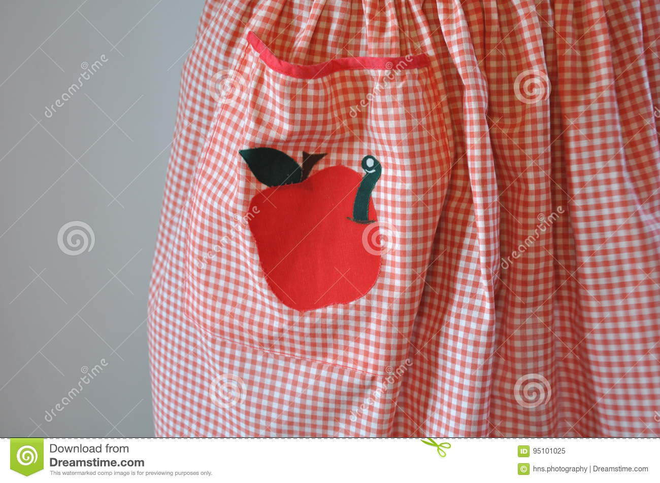 Red and white gingham apron with apple and worm applique stock image