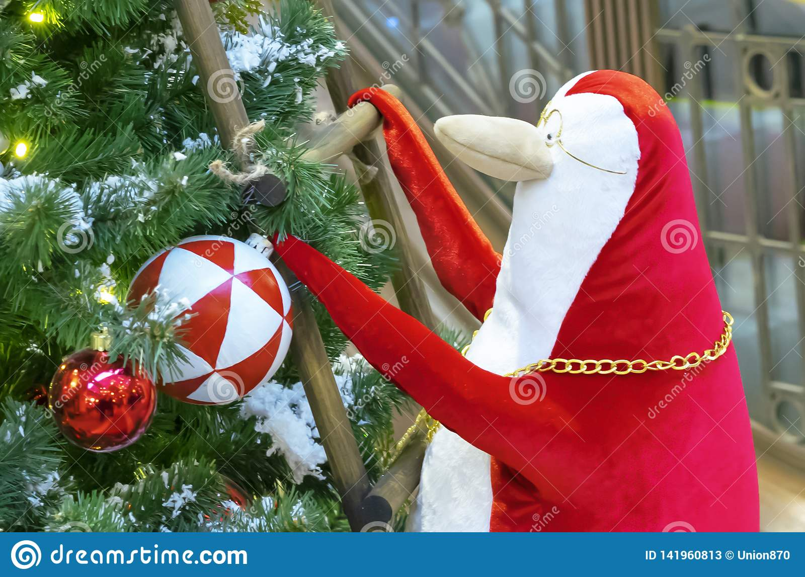 A red and white penguin climbs the stairs to the Christmas tree
