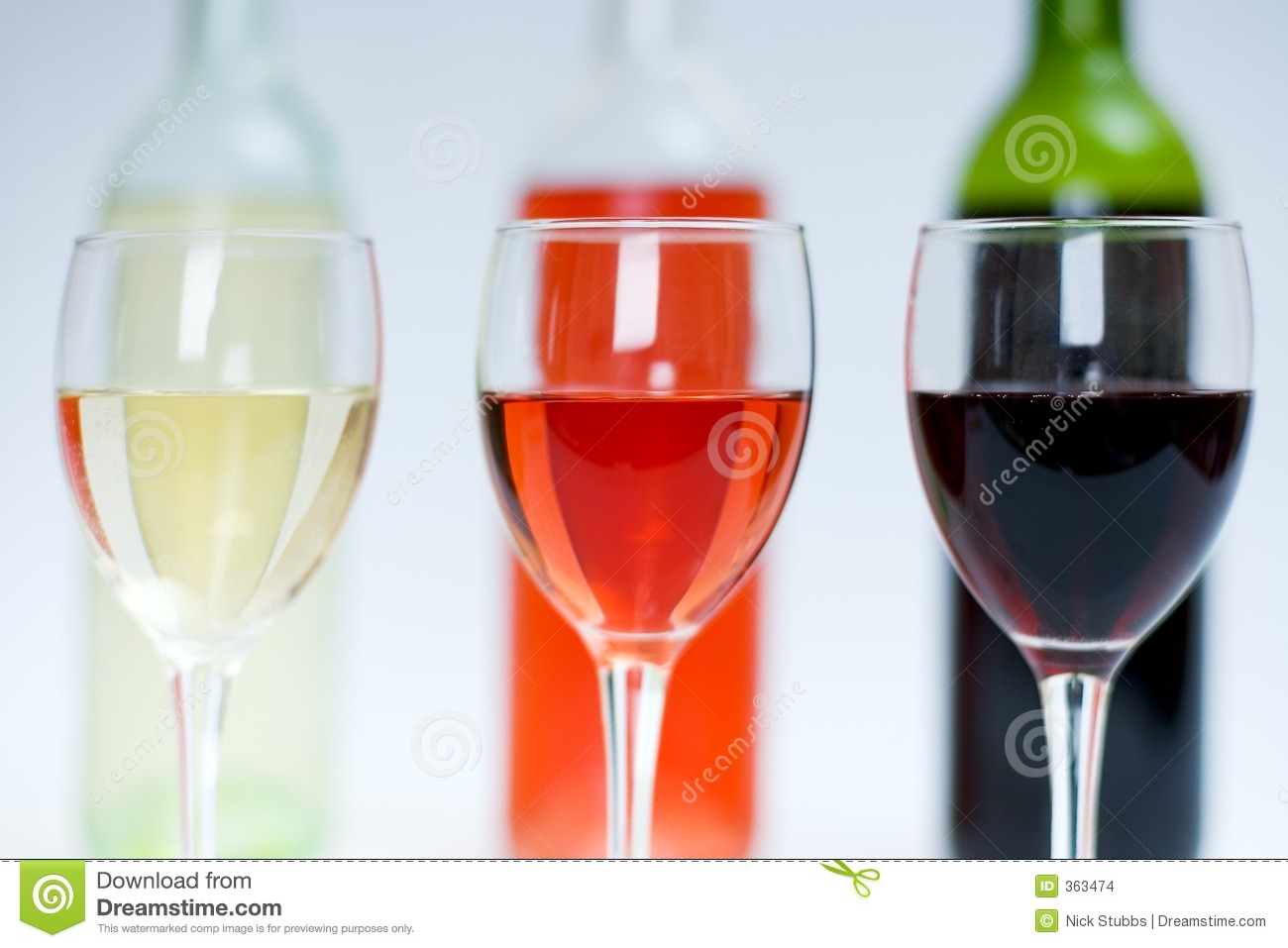 Red, white and rose wine in glasses with bottles behind