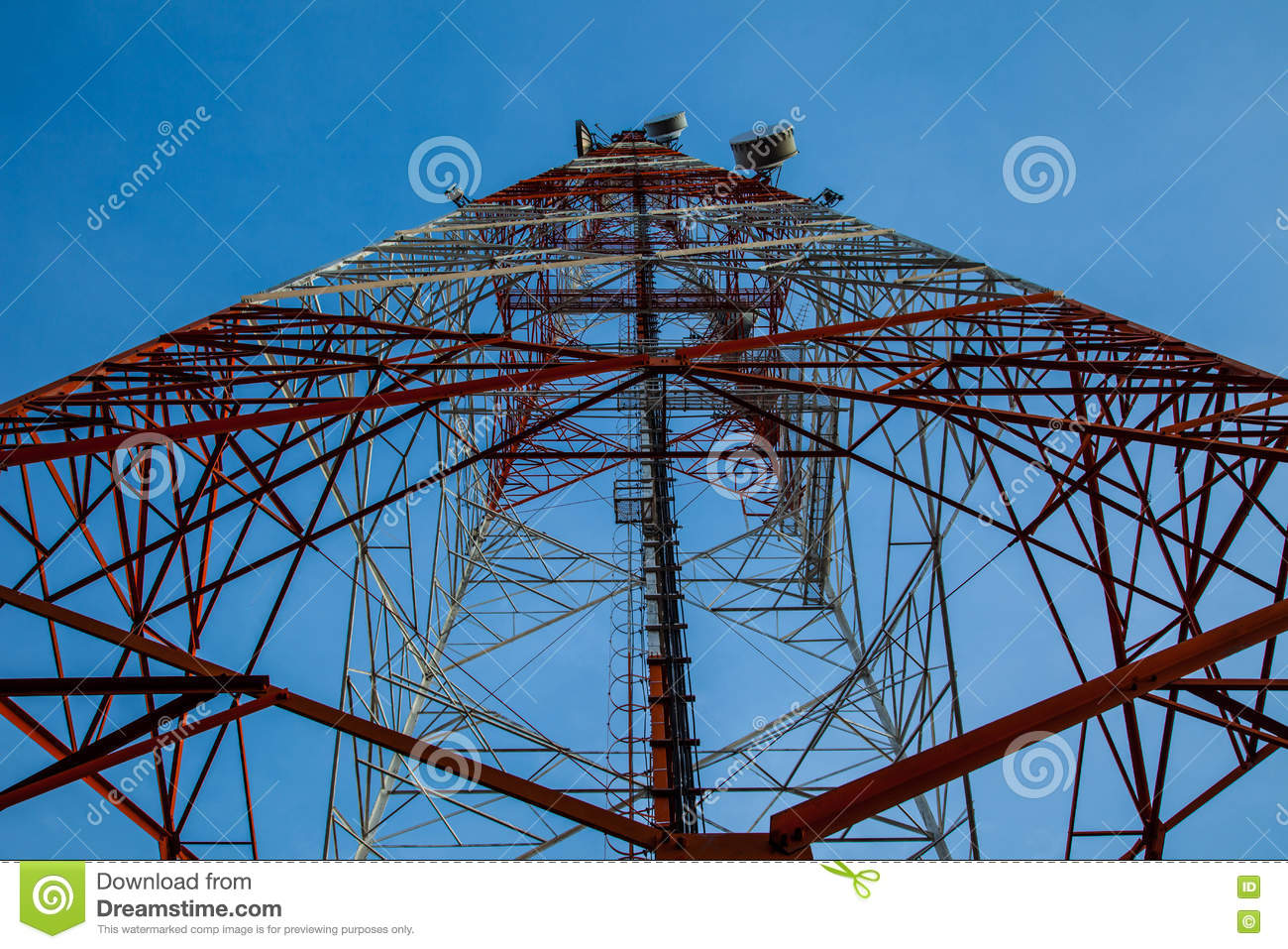 Red white telecommunication tower against blue sky - bottom view