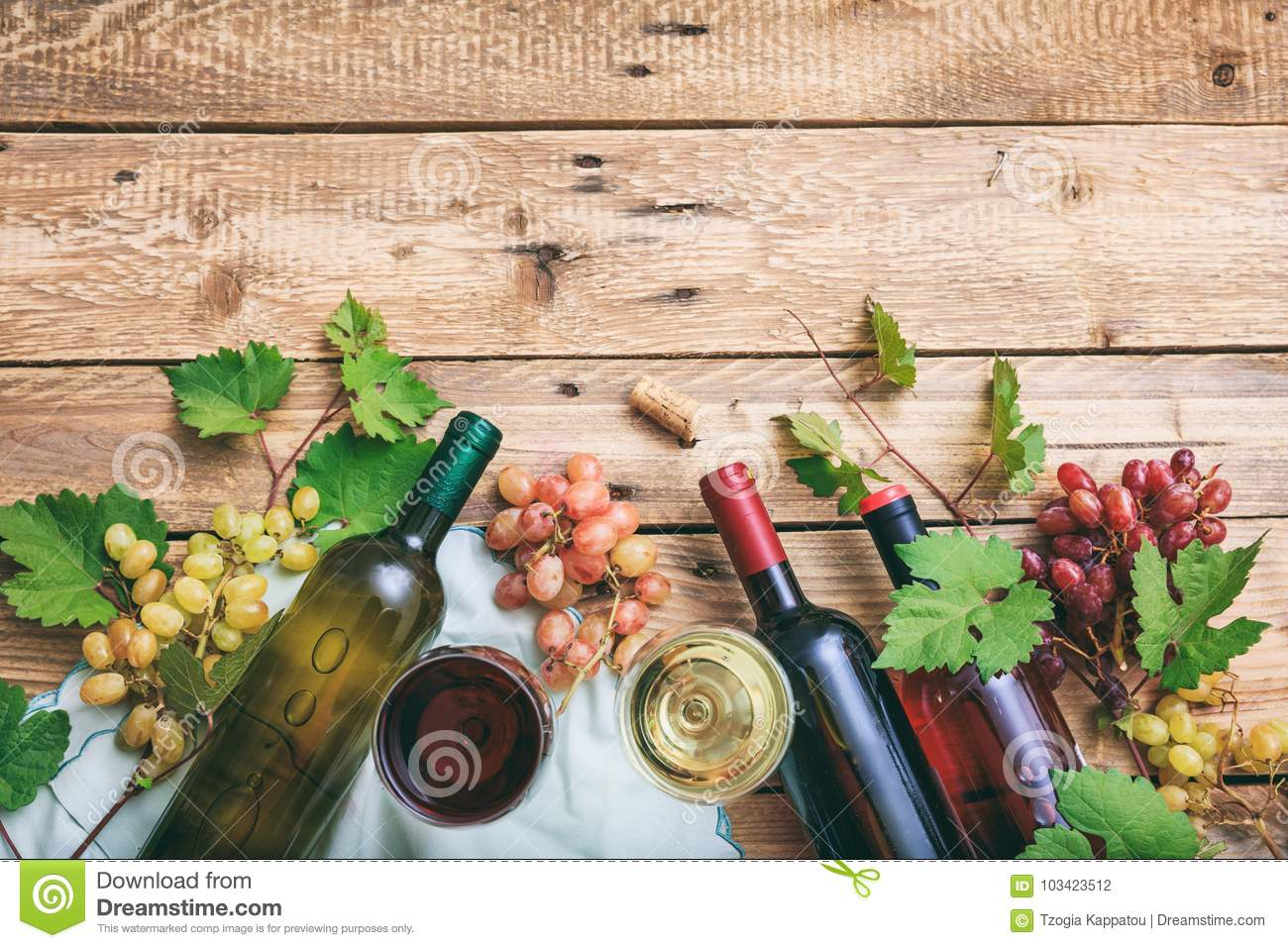 Red and white wine glasses and bottles on wooden background, copy space. Fresh grapes and grape leaves as decoration