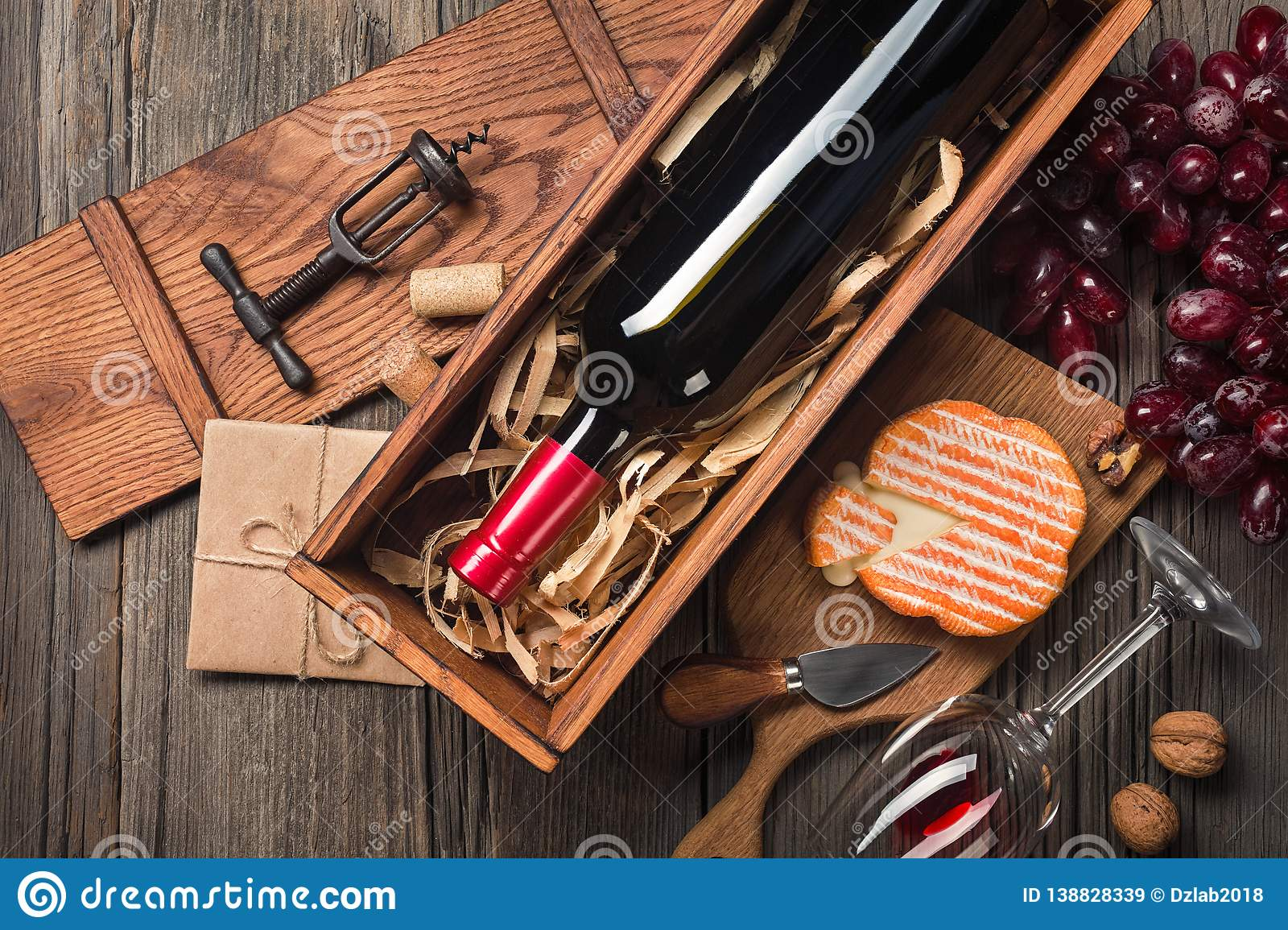 Red wine in a box with a glass, corkscrew and cream cheese on a wooden old table. Top view with space for your greetings