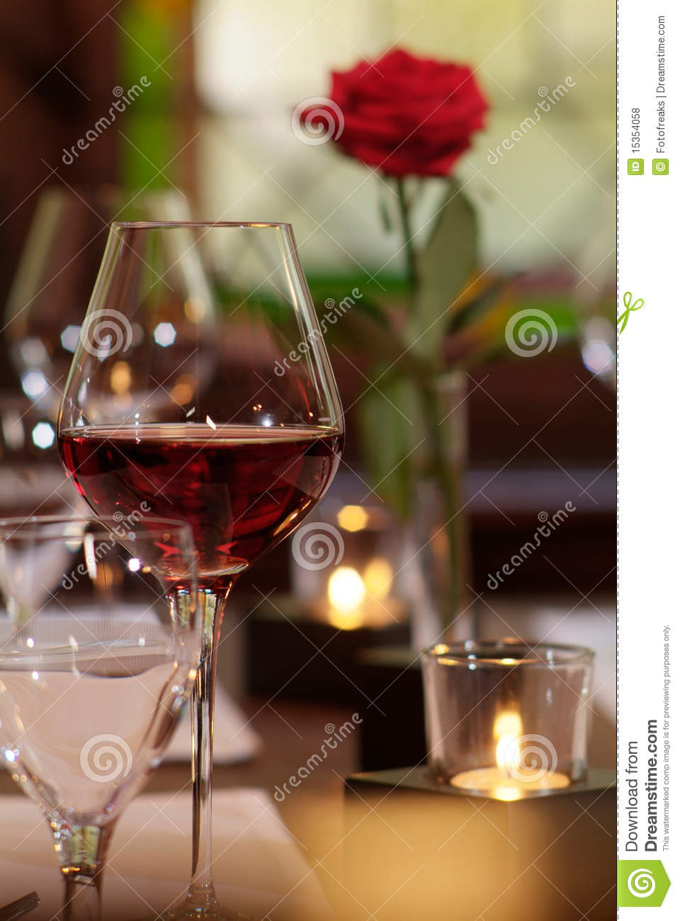 Red wine glass with candle and rose