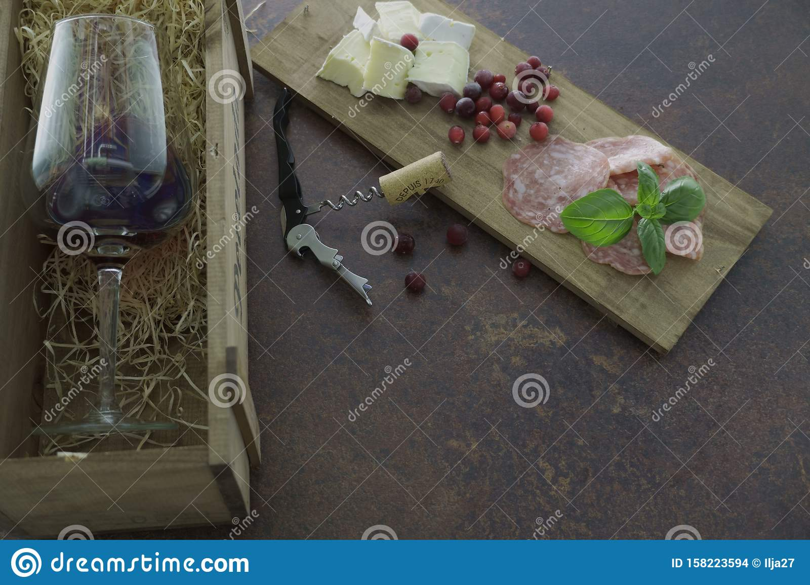 Red wine glass with cheese and salami in wooden box on concrete table