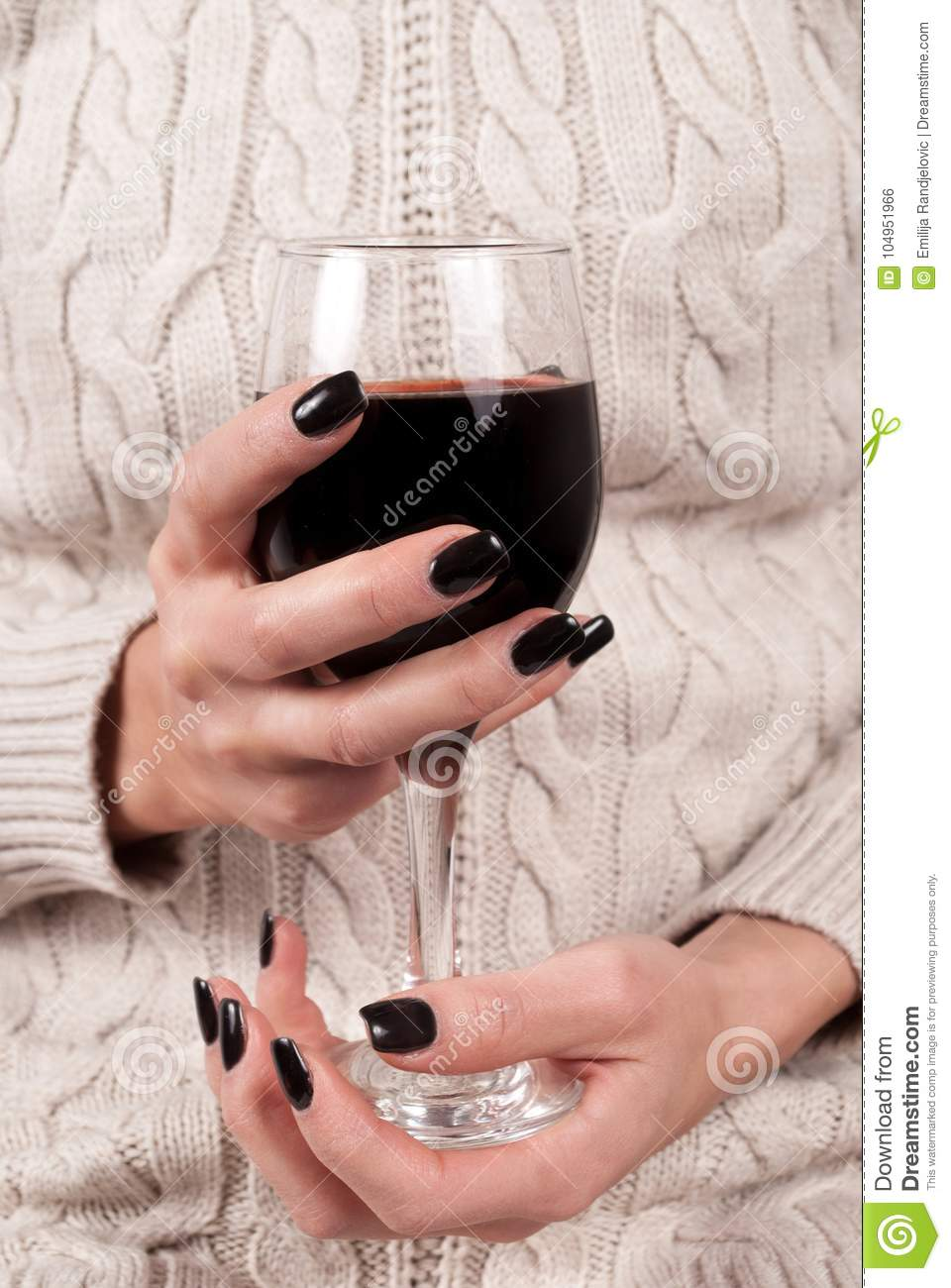 red wine glass in women hand with black nails and sweater stock photo
