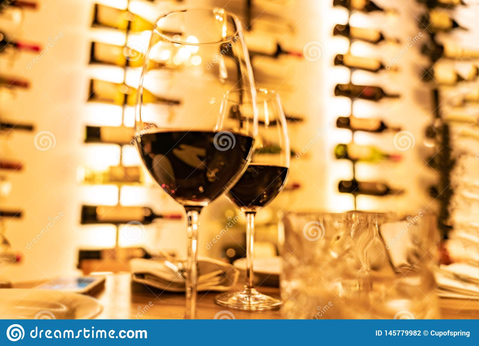 Red wine glasses on a wooden plank with defocused bottles rack in the background
