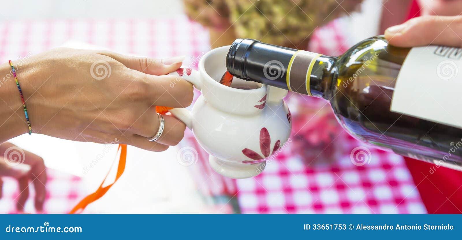 Red wine poured into ceramic jug