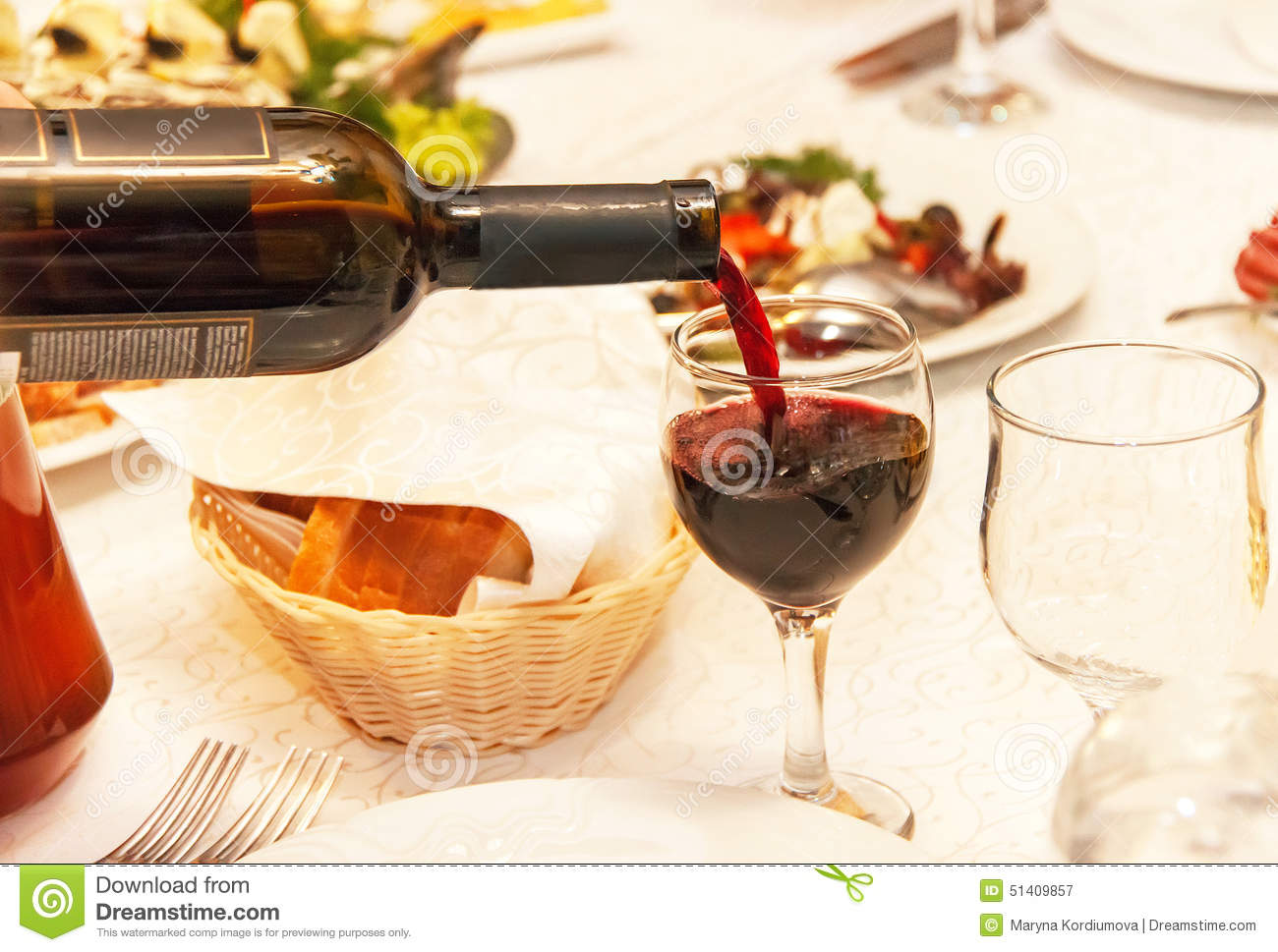 Red Wine Pouring Into A Wine Glass That Standing On The