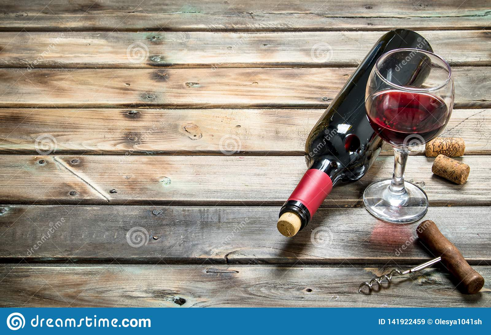 Red wine in a wine glass with a corkscrew