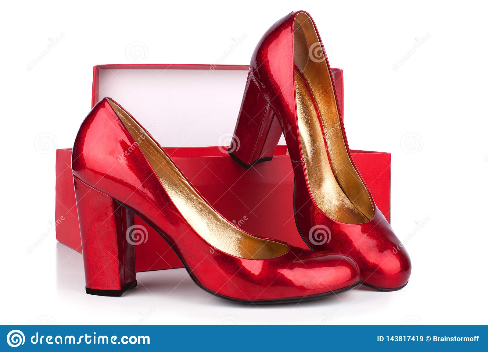 Red women`s high-heeled shoes patent leather and red box on a white background  close up