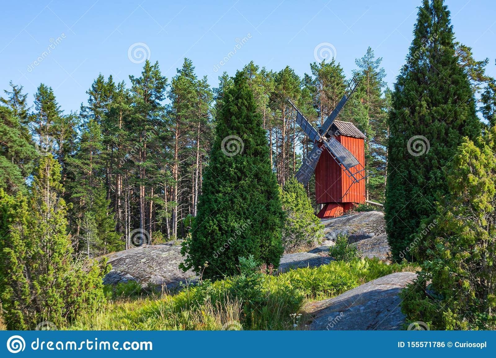 Red wooden windmill in a old vintage rural landscape at Aland islands, Finland. Jan Karlsgarden open air museum. Ethnographic park