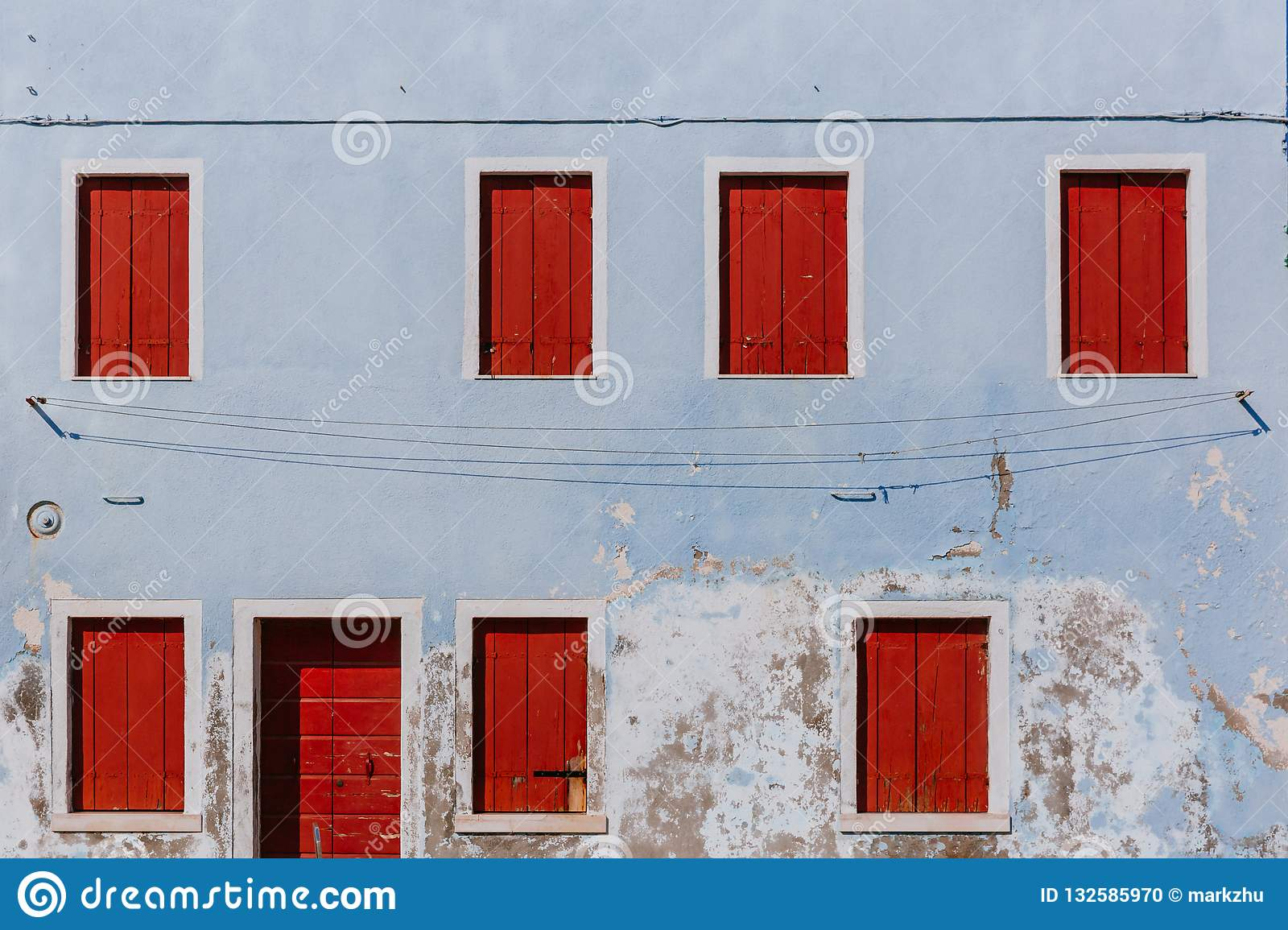 Red wooden windows and door on old light blue wall, on the island of Burano, in Venice, Italy