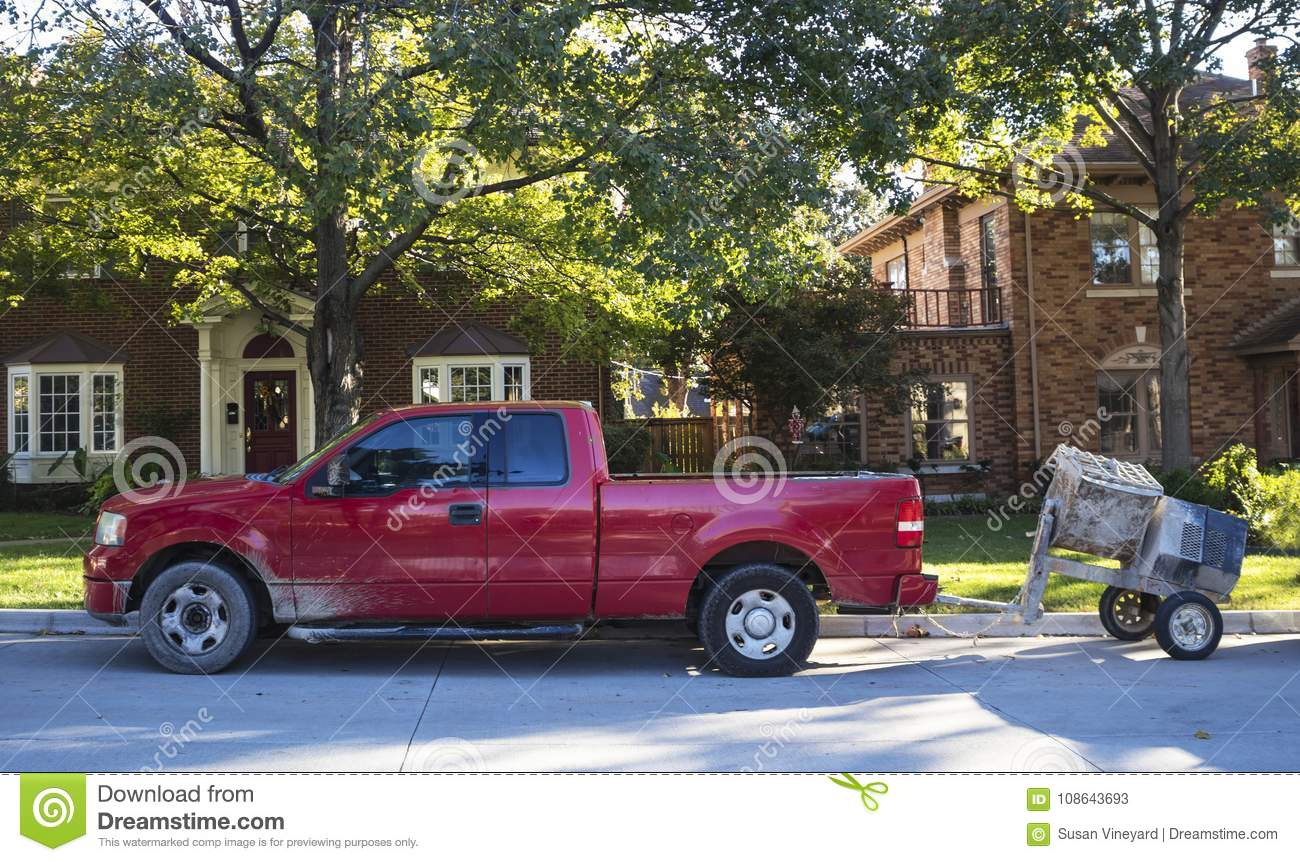 Red work pick up truck with cement mixer parked on street in traditional neighborhood