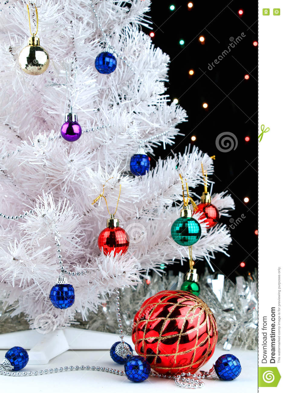 red christmas ball and blue balls garland near by white fir tree on blurred lights background