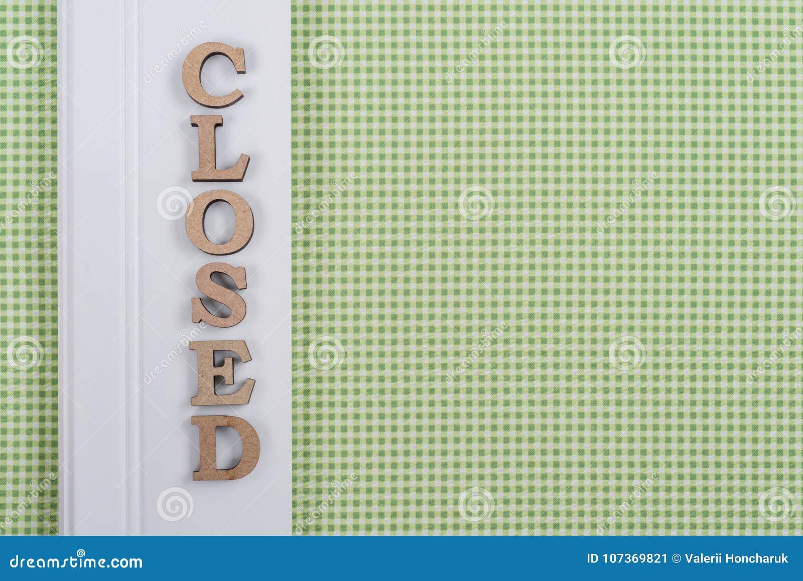 Redacte cerrado, letras de madera del extracto, fondo del blanco del verde