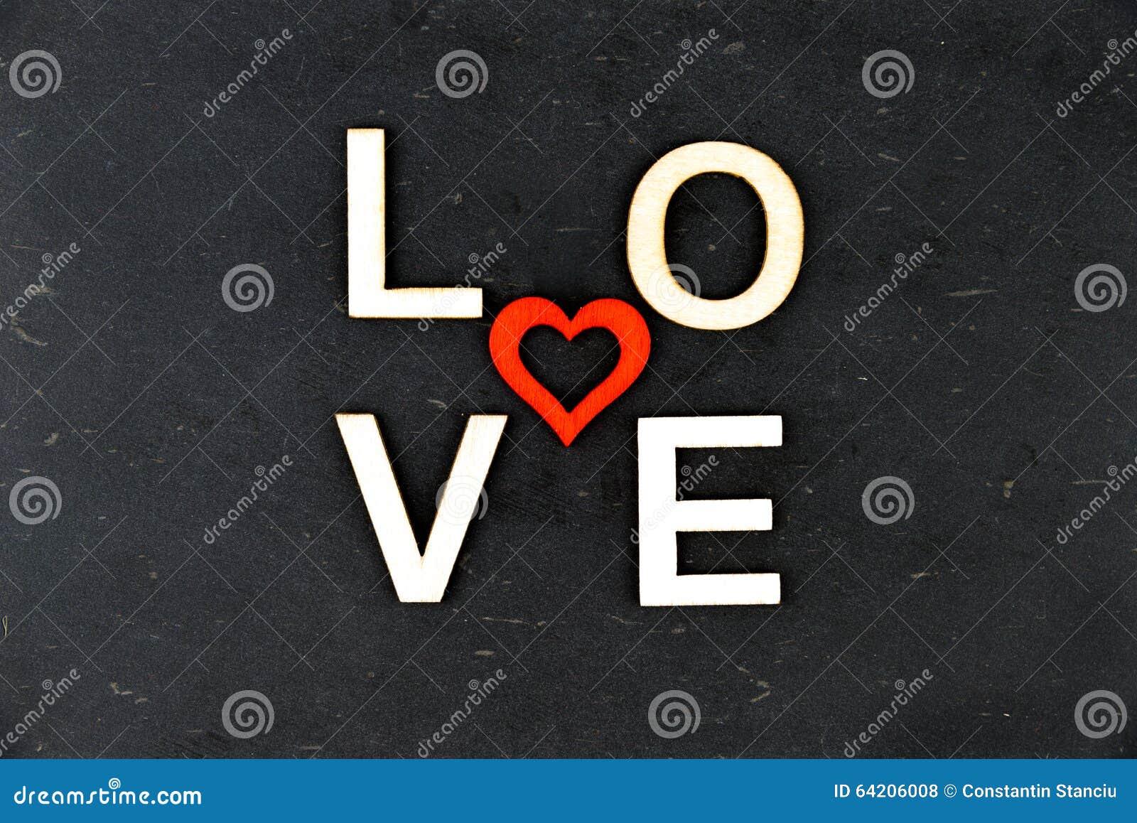 Redacte el AMOR creado de las letras de madera, forma de madera roja del corazón en el centro