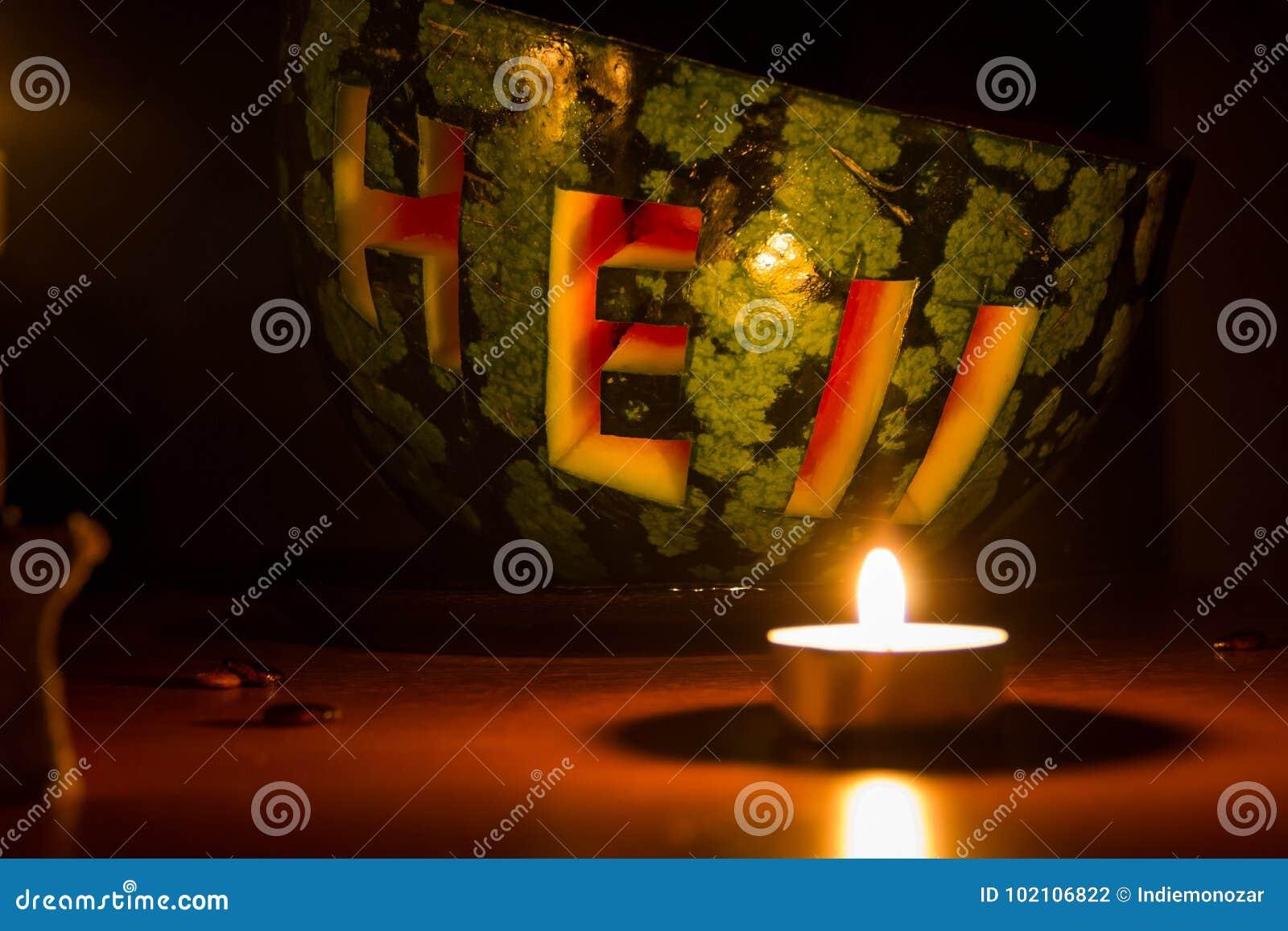 Redacte el infierno tallado en una sandía, velas ardientes y libros viejos en fondo oscuro