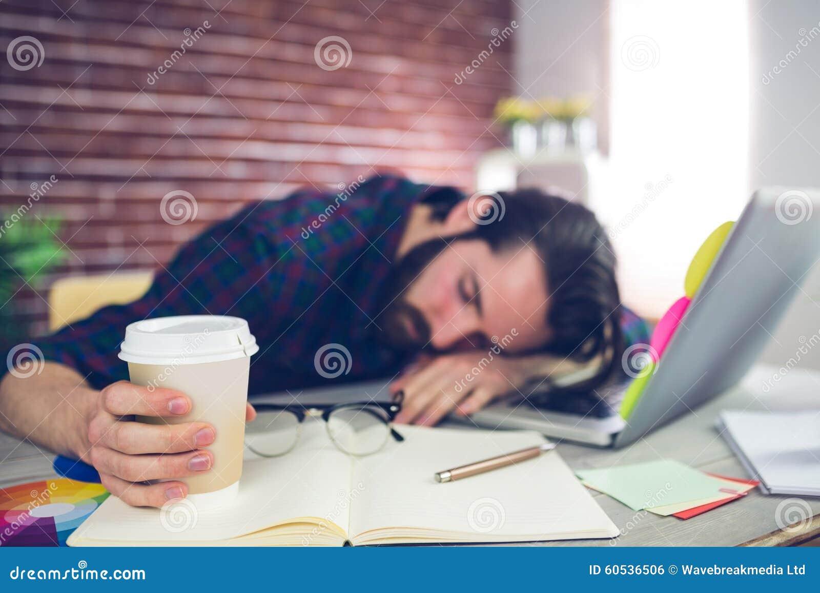 Redactor creativo cansado que sostiene la taza disponible