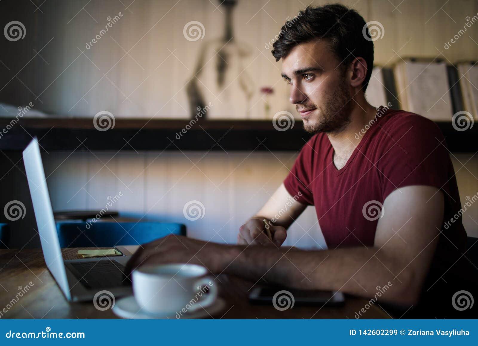 Redactor de anuncios acertado masculino que prepara un artículo para la publicación usando netbook