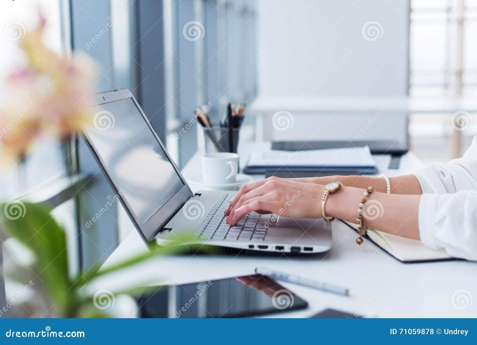 Redator fêmea em seu local de trabalho, casa, escrevendo o texto novo usando o portátil e a conexão a Internet de Wi-Fi na manhã