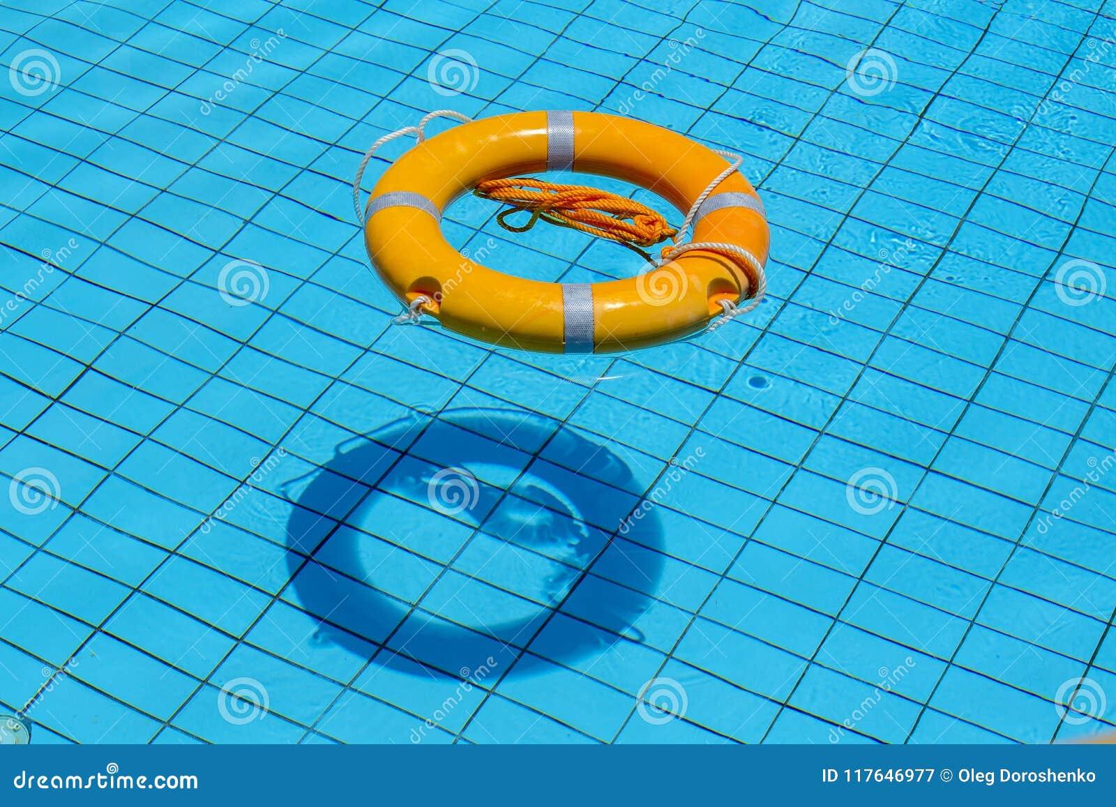 Reddingsboei die bovenop zonnig blauw water in zwembad drijven