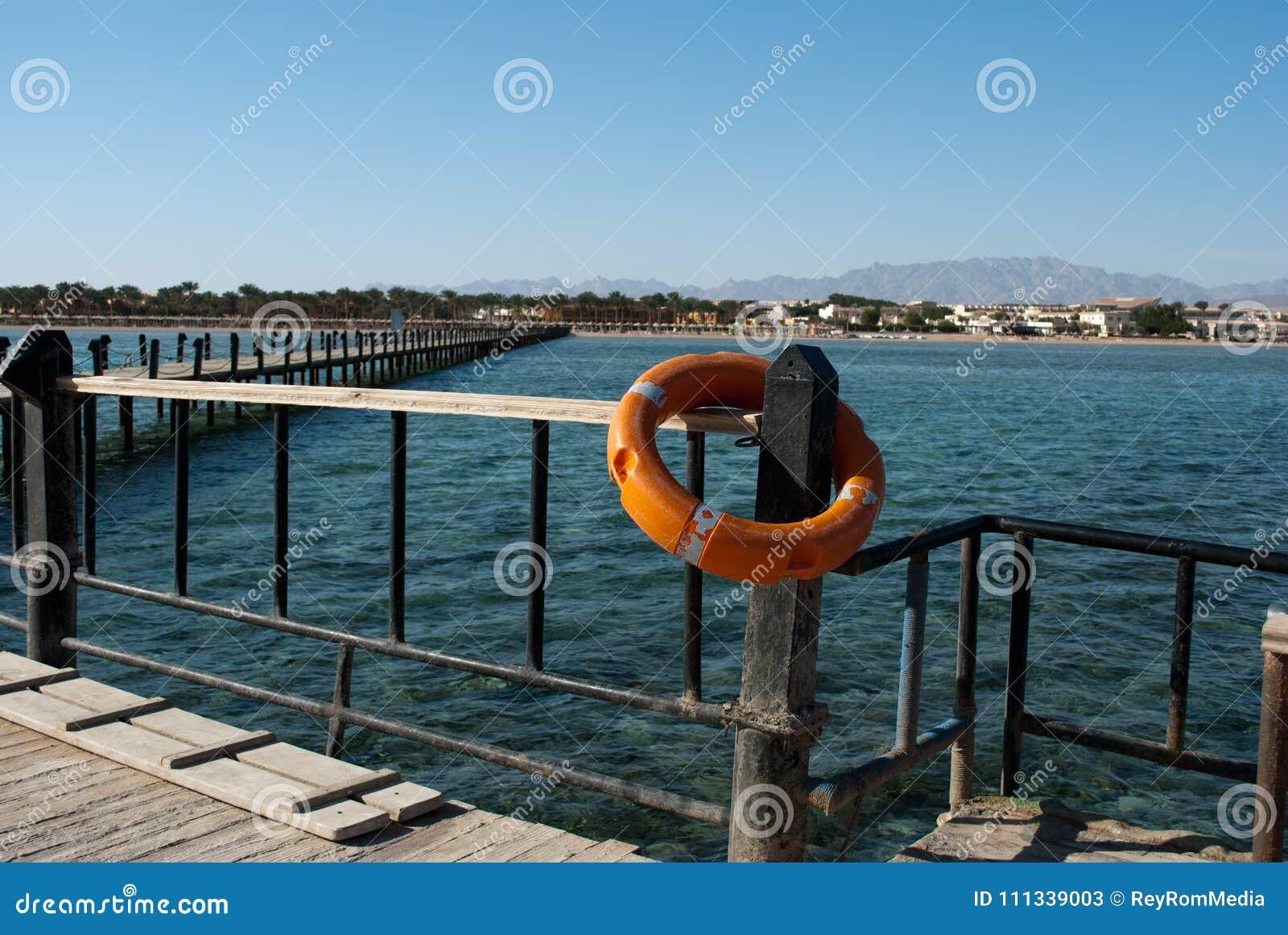 Reddingsboei en pijler Oranje reddingsboei op barrièrepijler Sparen reddingsboei en blauw water Veiligheidsmateriaal op dok voor