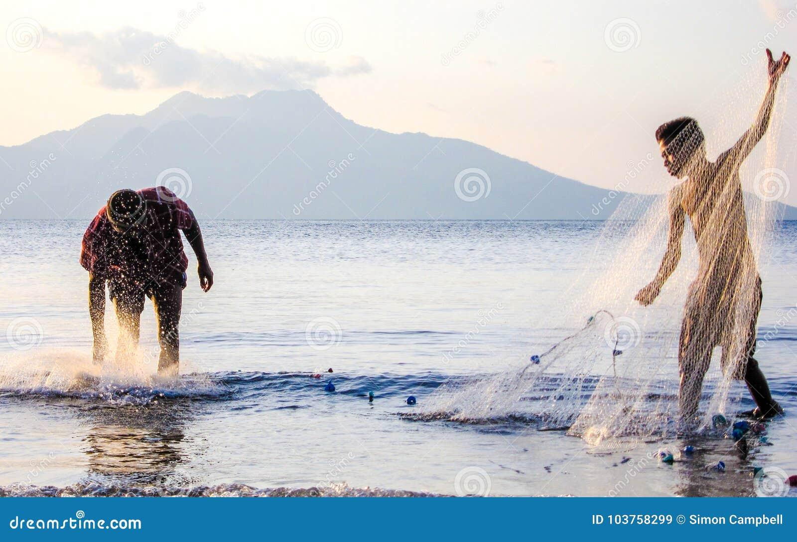 Redes de pesca en la puesta del sol, el pescador local y el aprendiz joven, Flores, Indo, Asia