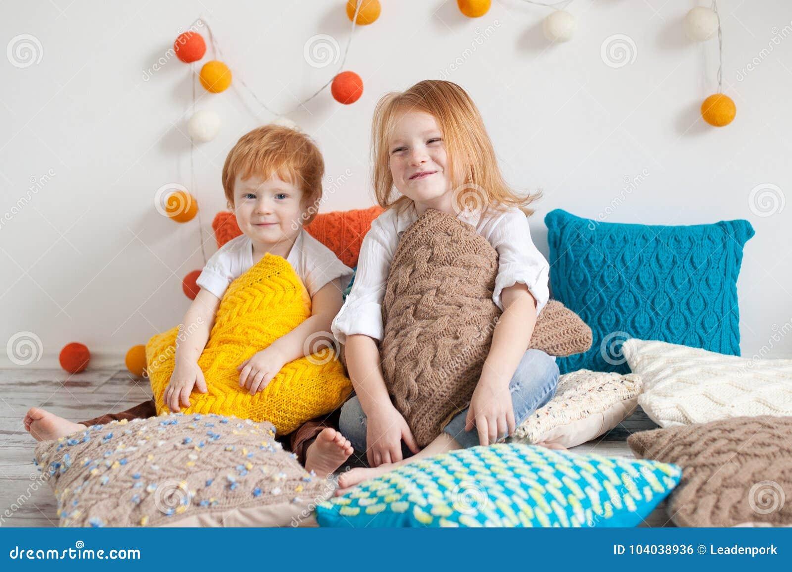 Redhaired дети среди подушек