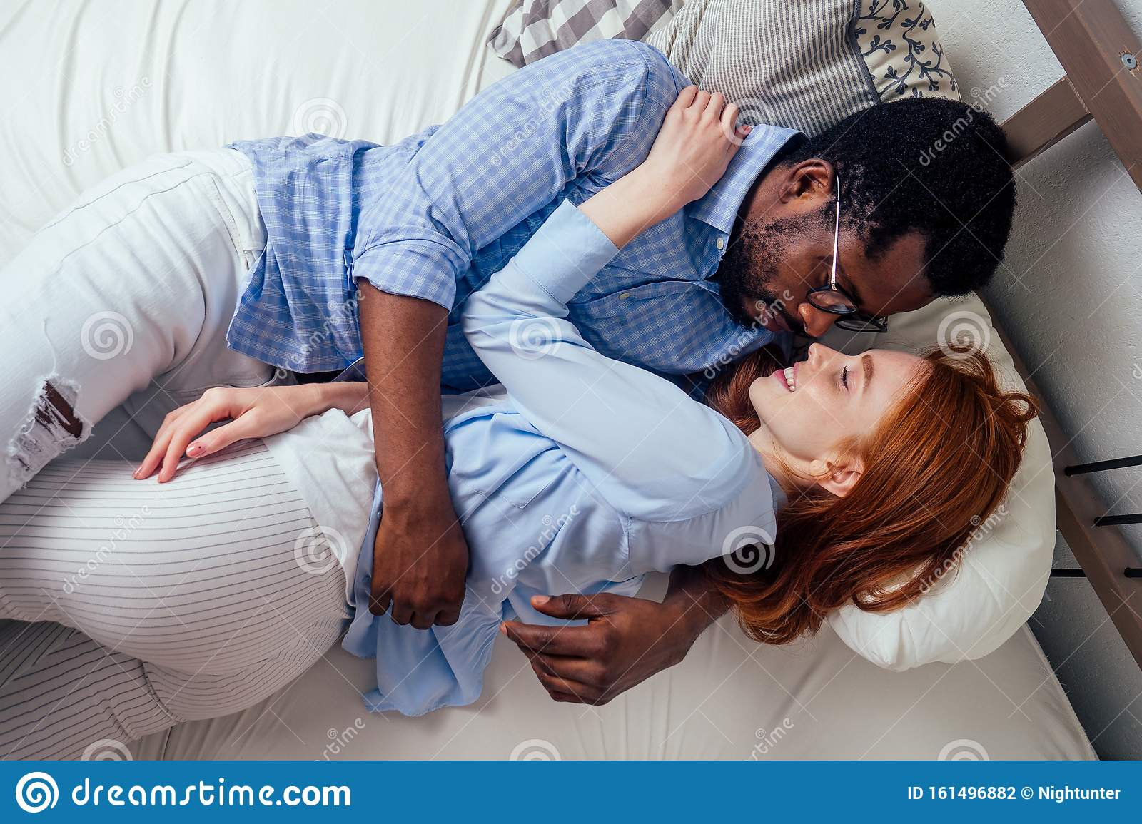 Redhaired Ginger Caucasian Happy Female And Multi Ethnic Afro Man Together Lying In Bed Bedroom Lifestyle Tolerance Stock Photo Image Of International Kiss 161496882
